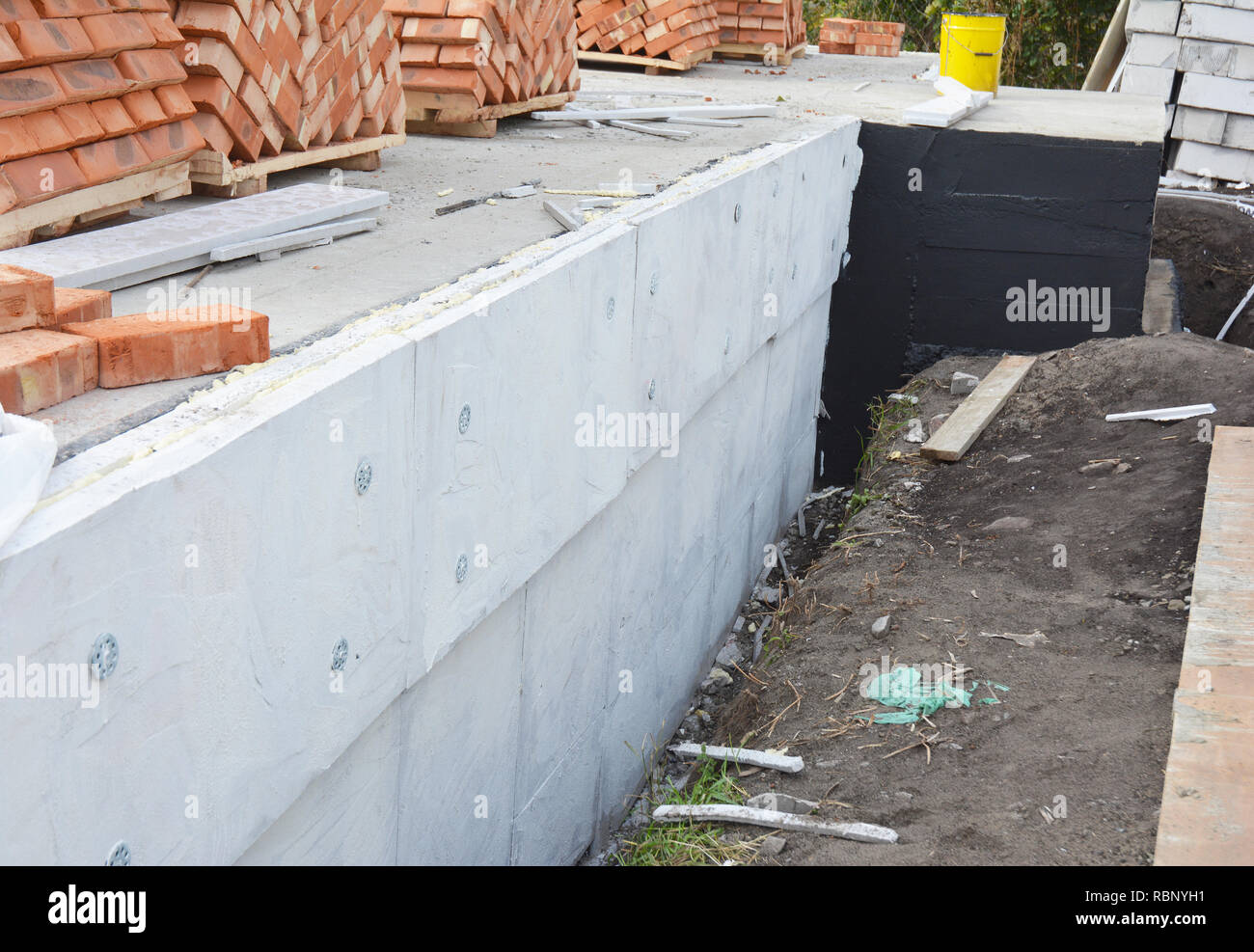 Insulating Exterior Foundation Walls. Foundation Waterproofing and Damp proofing Coatings. Waterproofing house foundation with spray on tar with insul - Stock Image