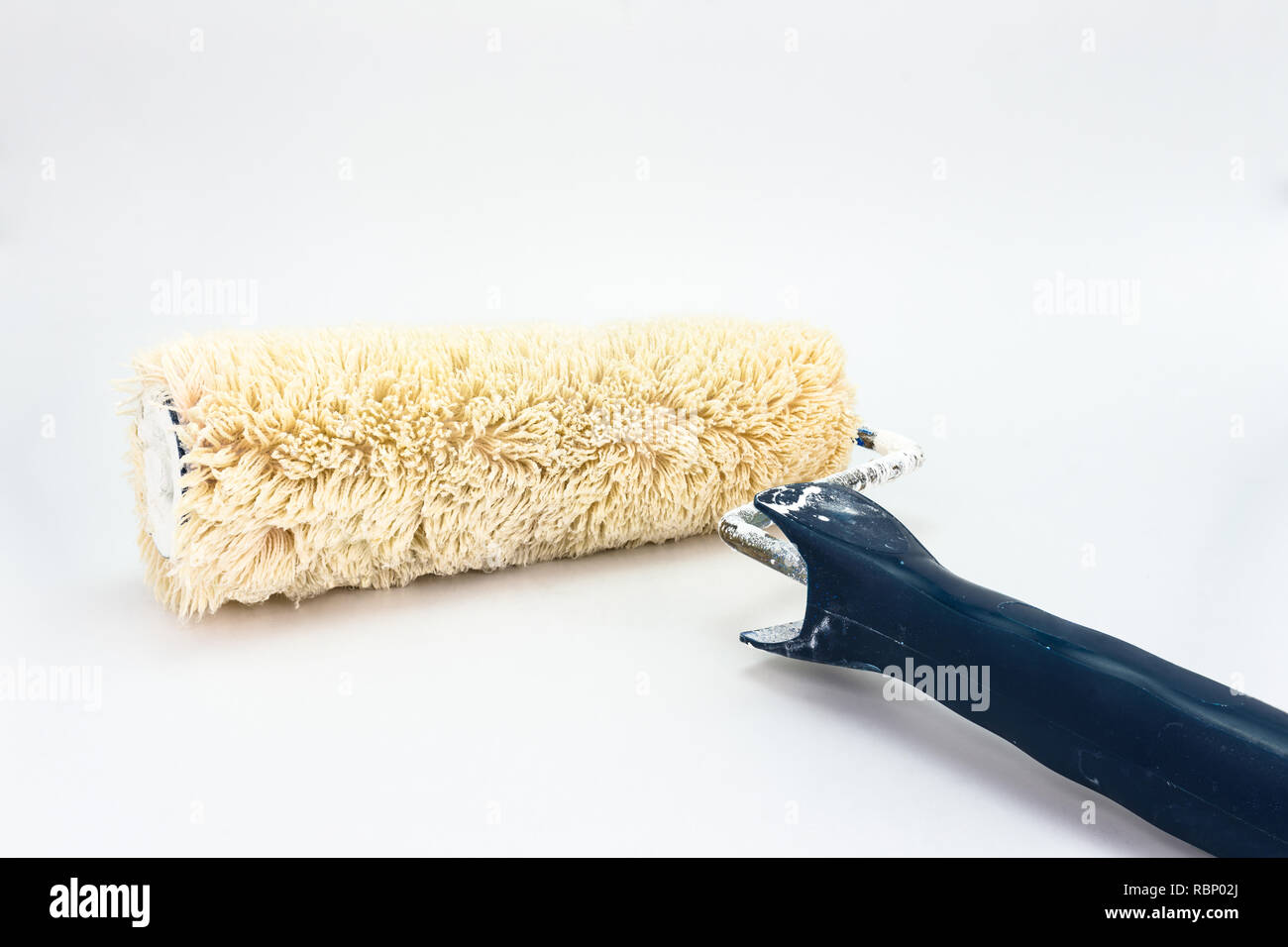 Used, dirty paint roller with a blue handle. Isolated on a white background with a clipping path. - Stock Image
