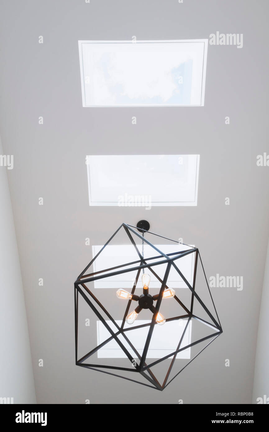 Skylight windows and black steel hexagonal lighting fixture with five clear glass bulbs hung above the staircase inside a modern cube style home - Stock Image