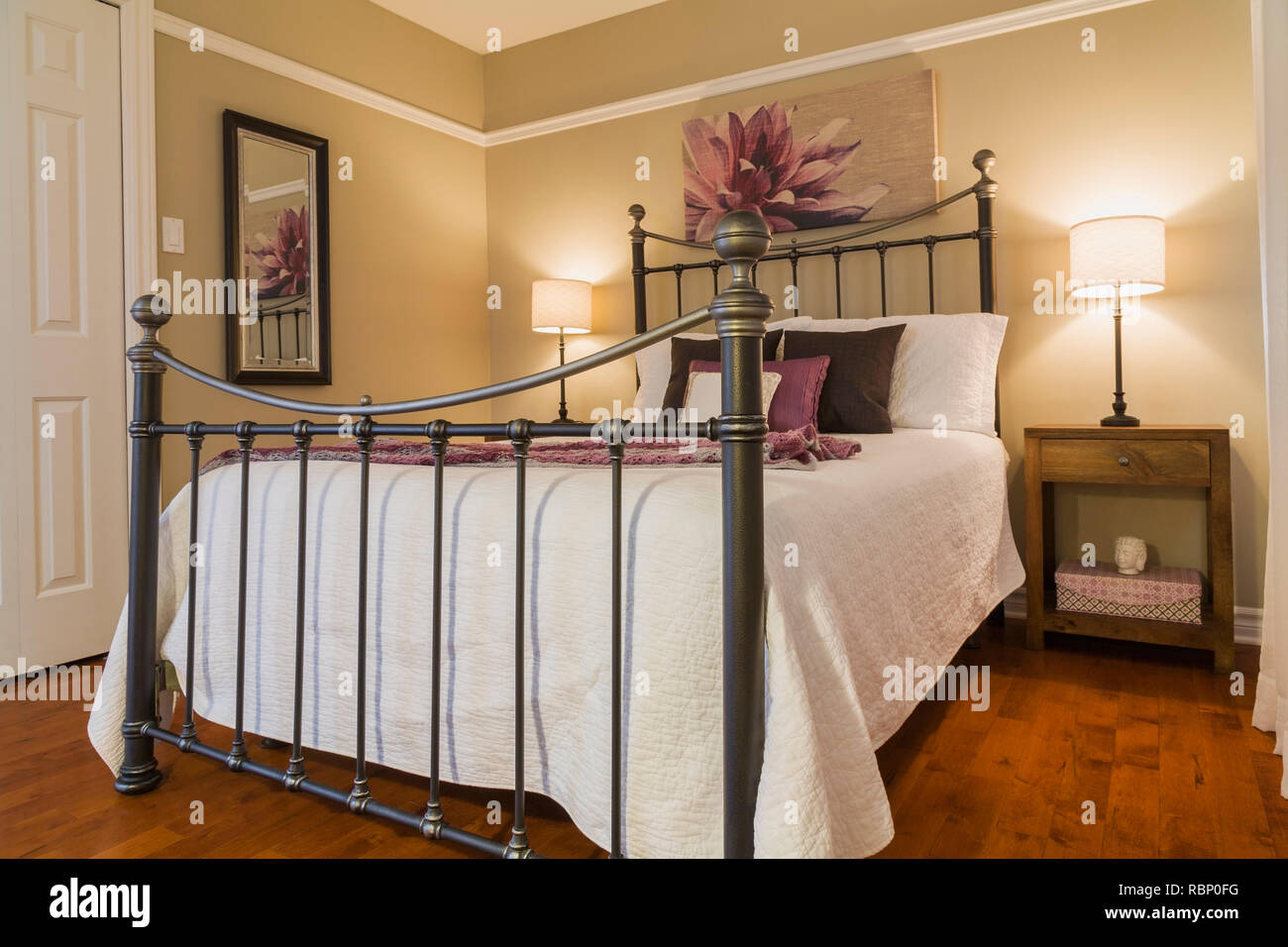 Queen Size Bed With White Bedspread And Antique Wrought Iron