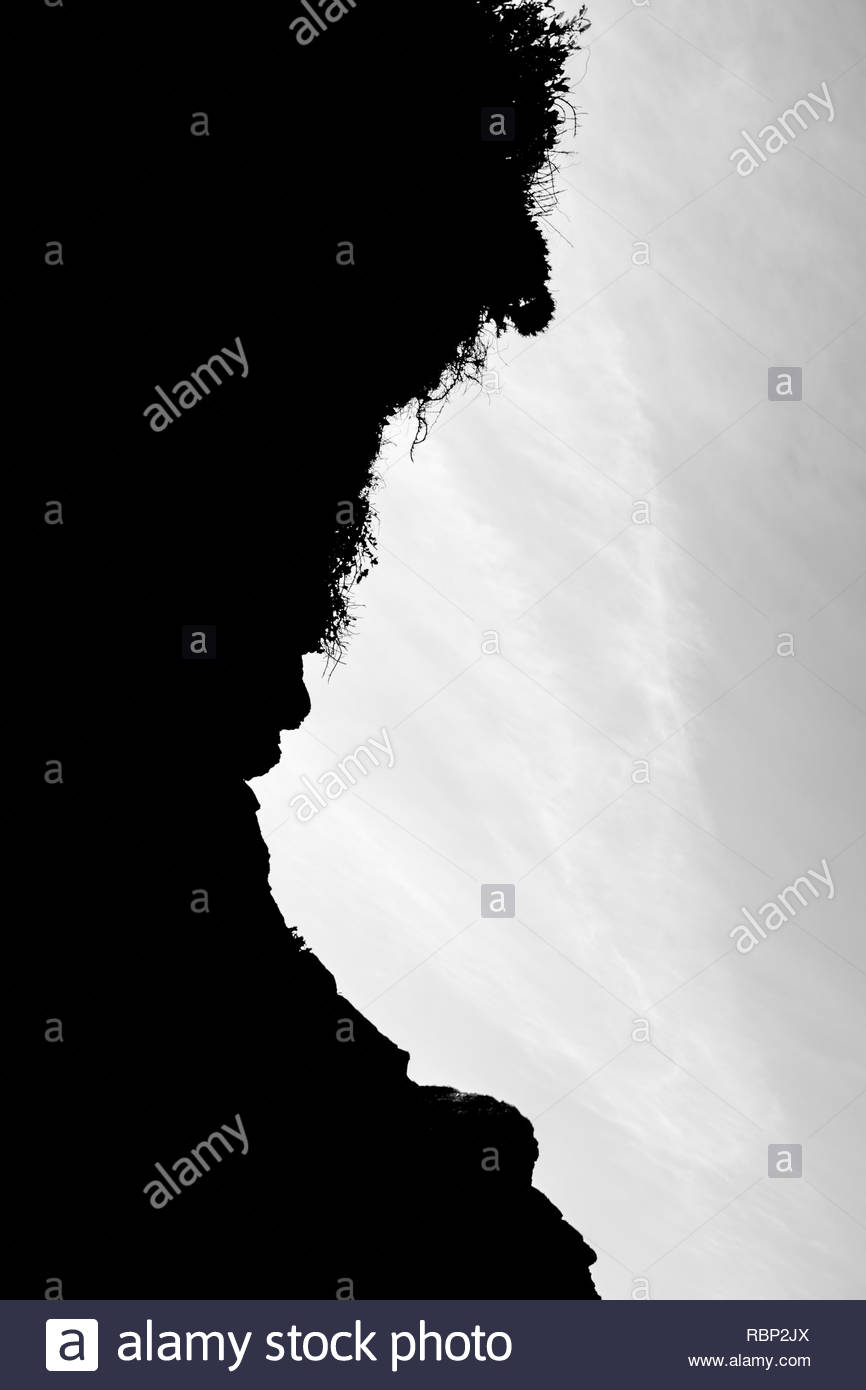 Rock silhouette against sky - Stock Image