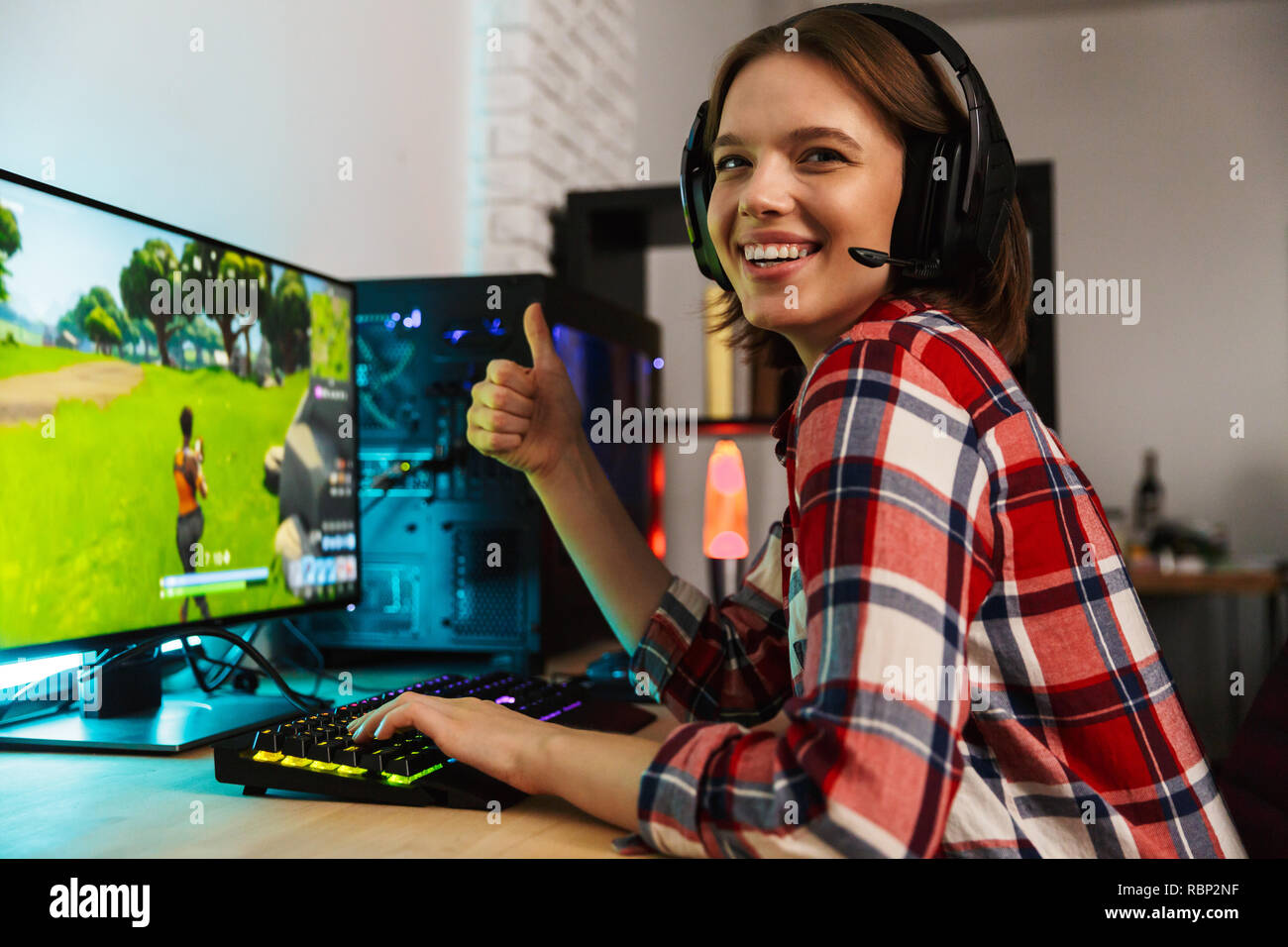 Portrait of an excited young woman wearing headphones sitting at the table, playing computer online games Stock Photo