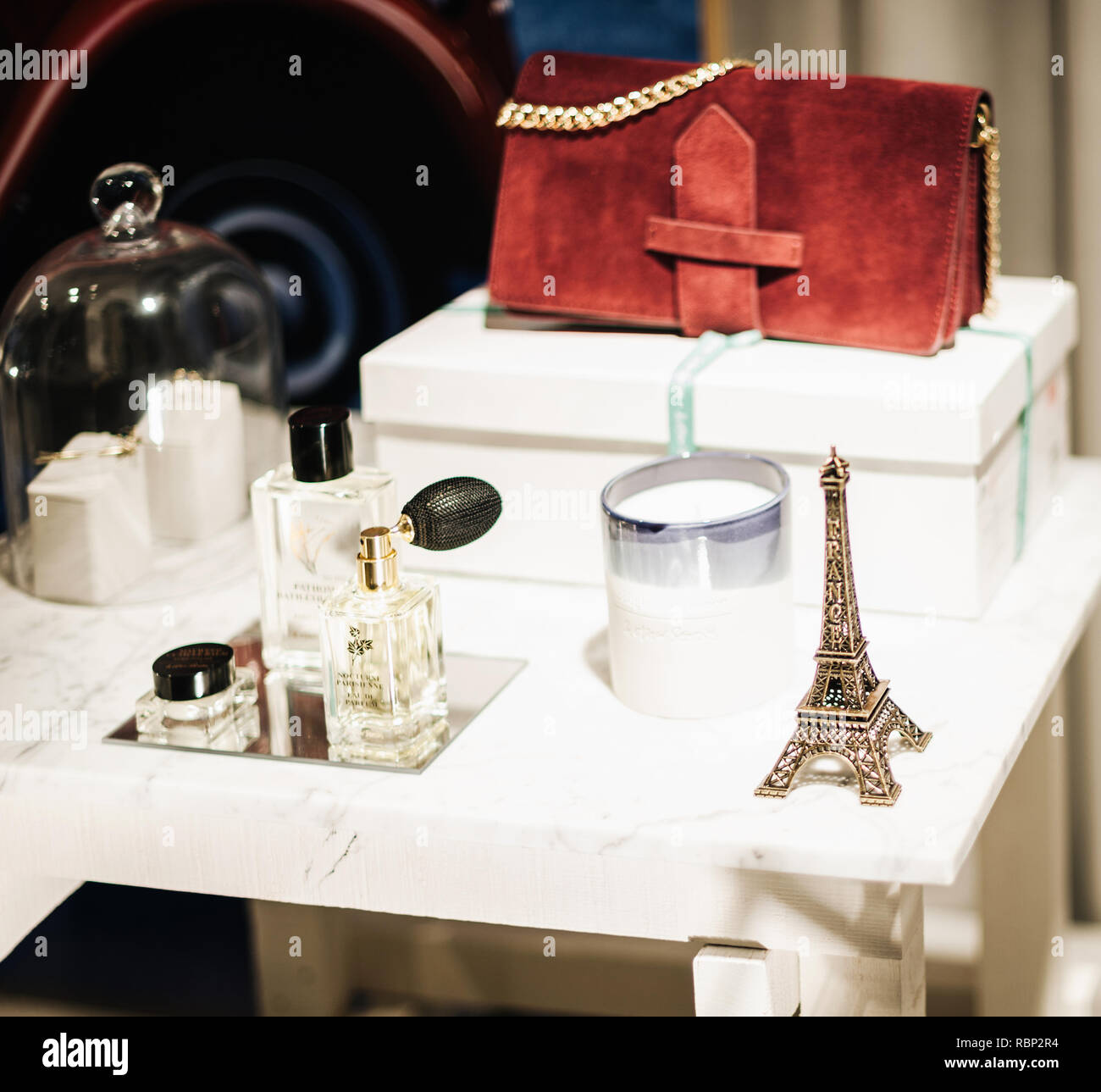 STRASBOURG, FRANCE - DEC 23, 2016: Fashionable setting of luxury perfume, purse, candle, Eiffel Tower silhouette in the fashion store in Paris - Stock Image