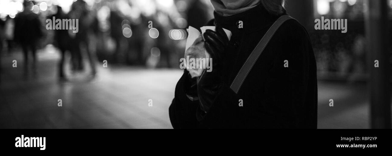 Woman eating Traditional Christmas food with defocused blurred Christmas market in the background Stock Photo