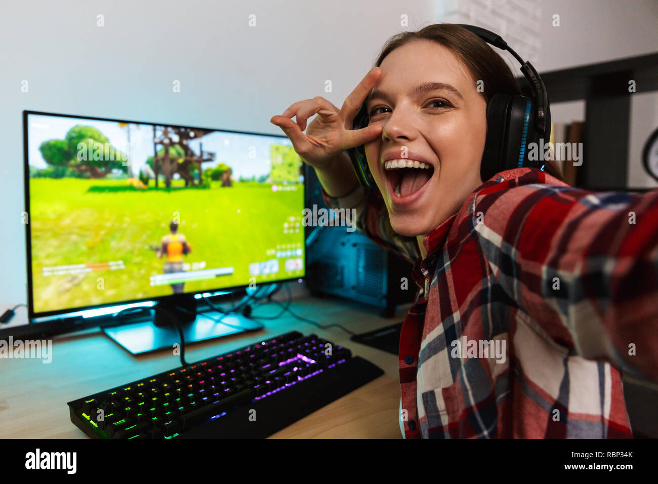 Portrait of an excited young woman wearing headphones sitting at the table, playing computer online games, taking a selfie Stock Photo