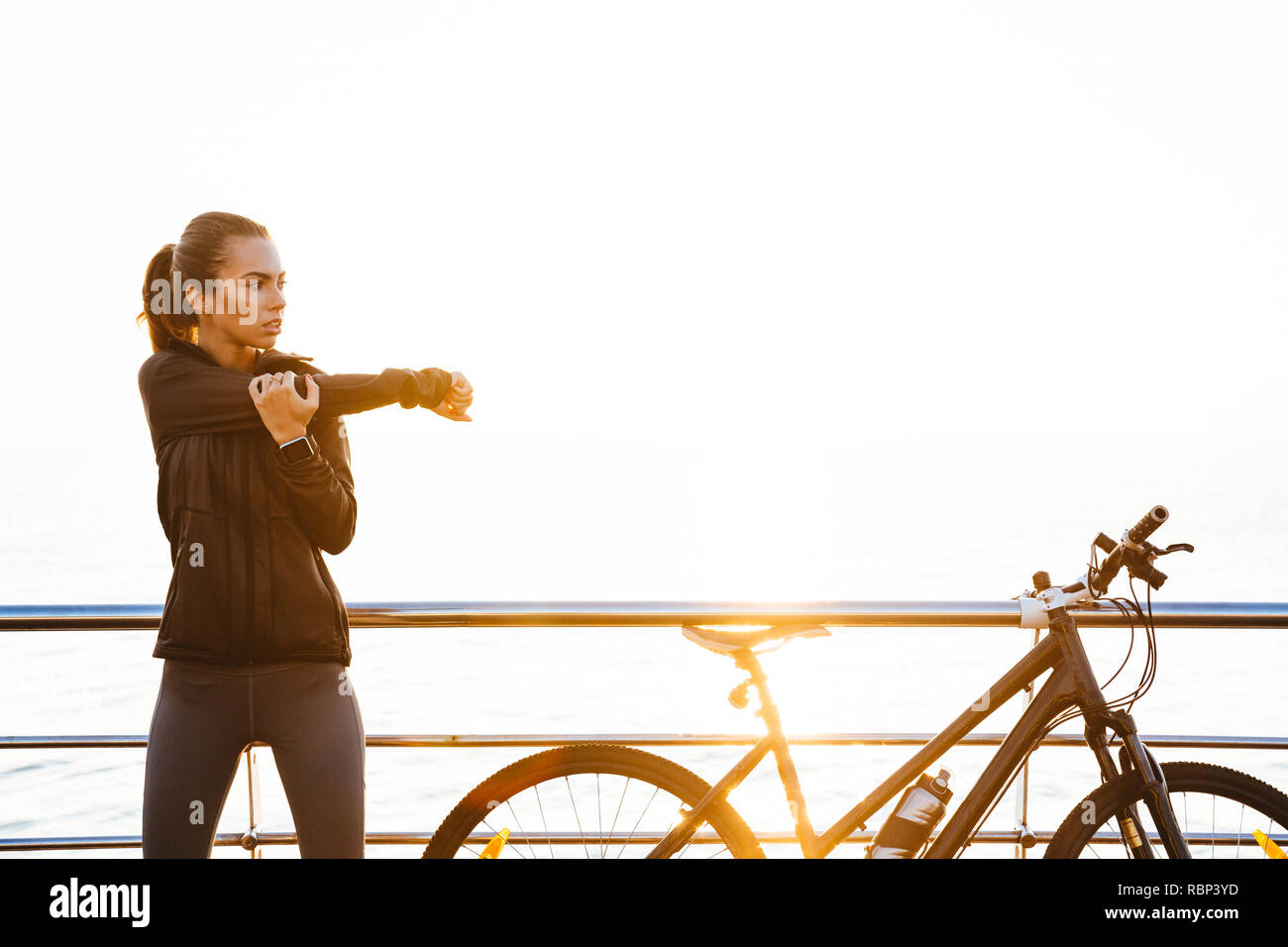 Photo of sporty woman doing stretching exercises while standing near bicycle outdoors during sunrise over ocean Stock Photo