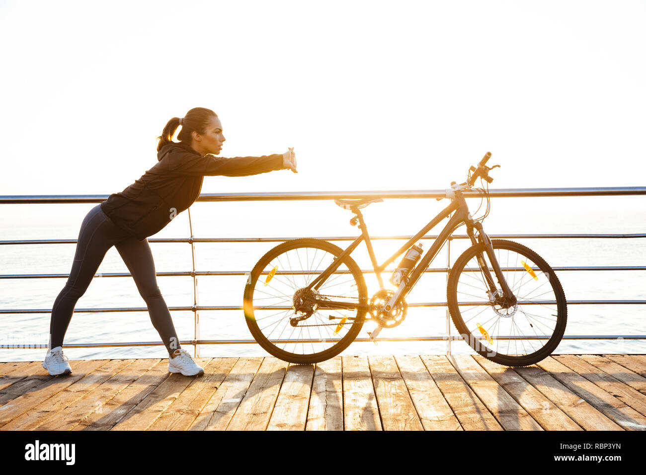 Photo of athletic woman doing stretching exercises while standing near bicycle outdoors during sunrise over ocean Stock Photo