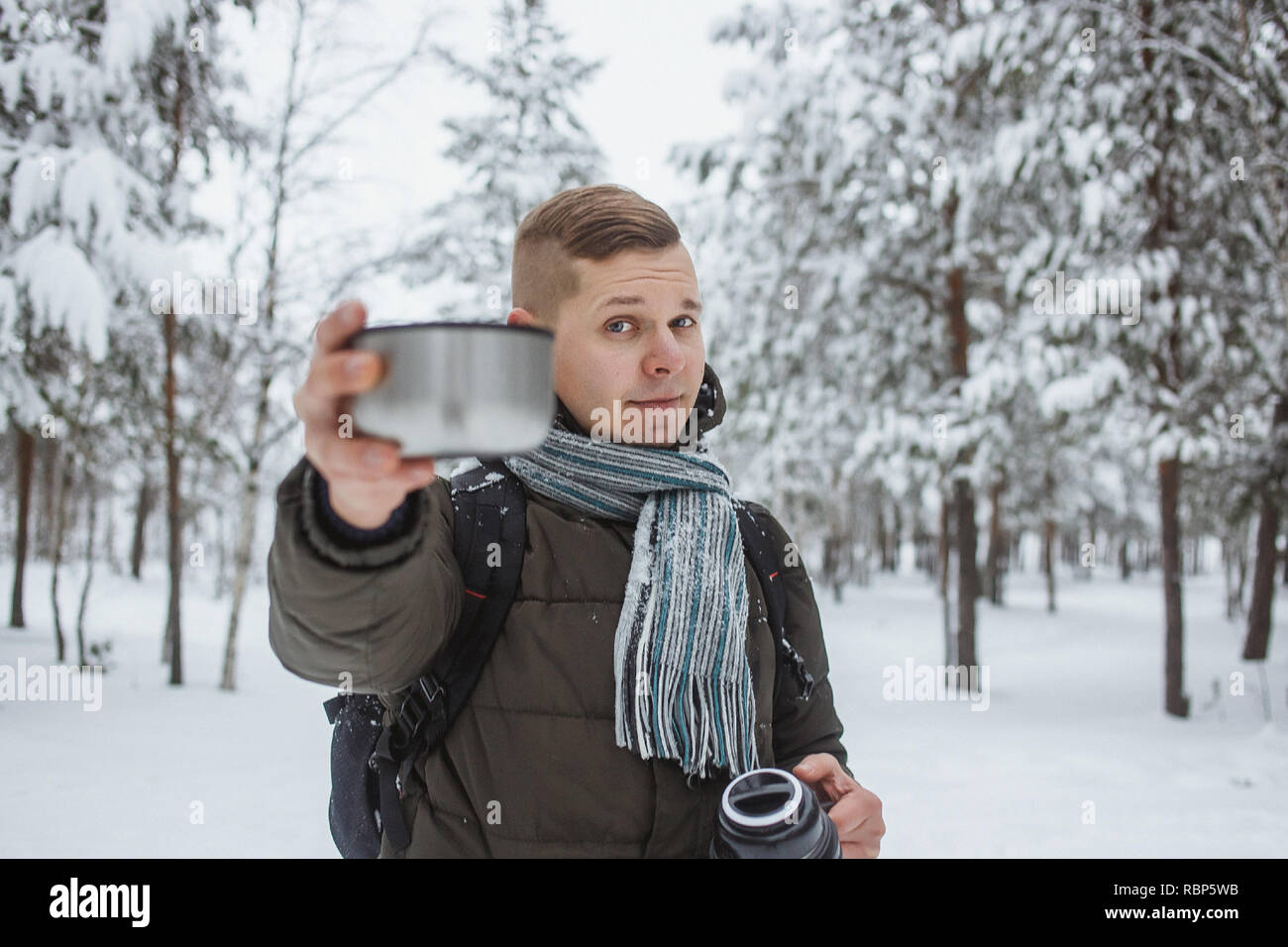 Stylish man with a thermos of hot tea in a snowy conifer forest. - Stock Image