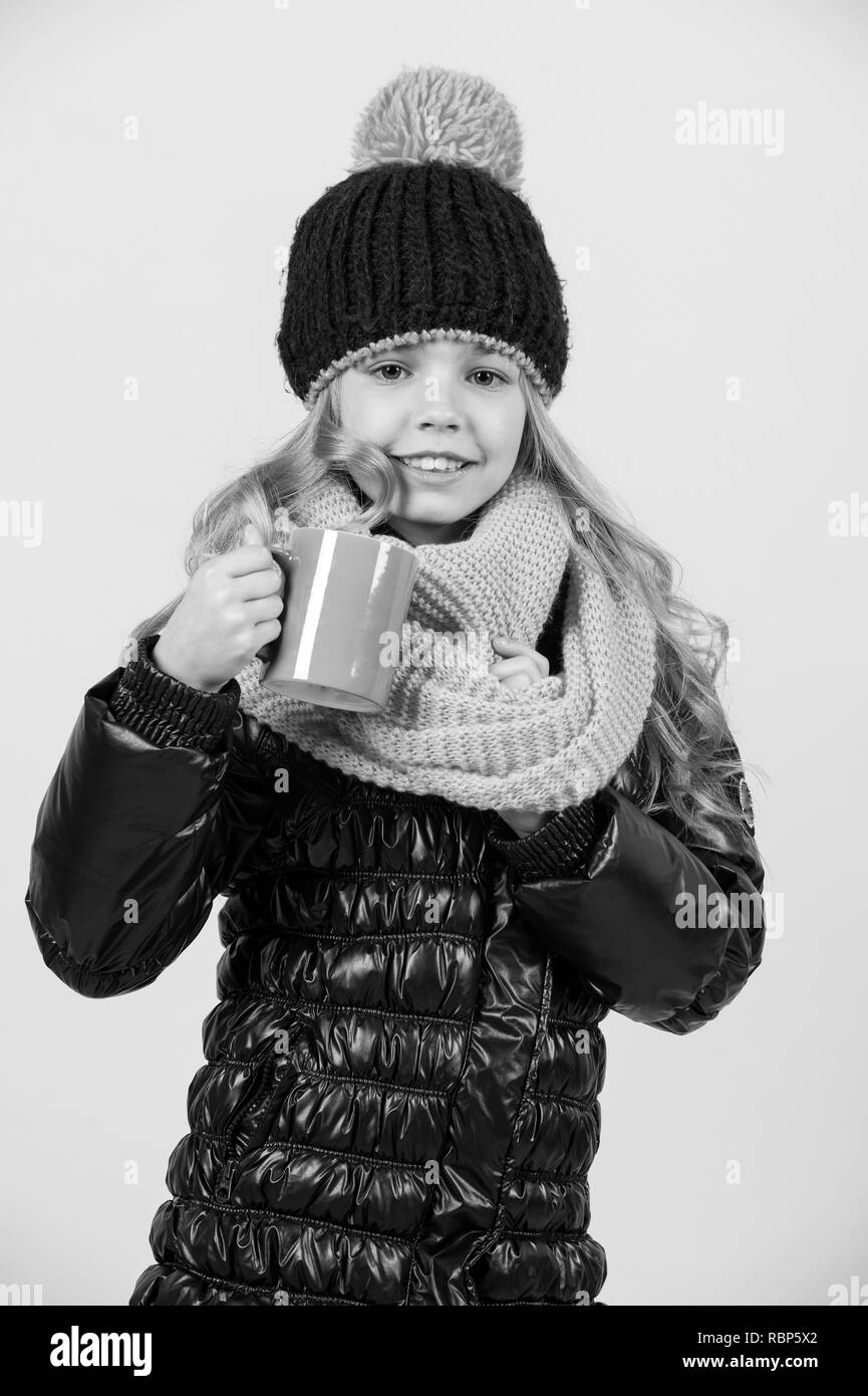 Hot drink in cold weather. Girl in hat, pink scarf, black jacket with mug. Autumn season relax concept. Tea or coffee break. Child with blue cup smile on orange background. - Stock Image