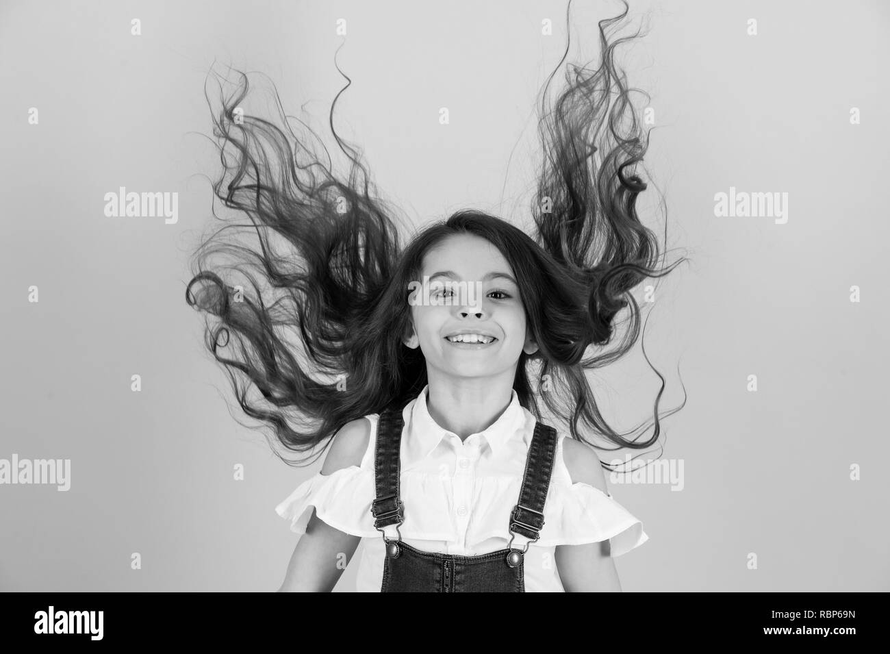 Haircare, hairstyle, hairdresser, barber. Girl smile with flying hair on blue background. Child smiling with long healthy hair. Beauty salon concept, punchy pastel - Stock Image