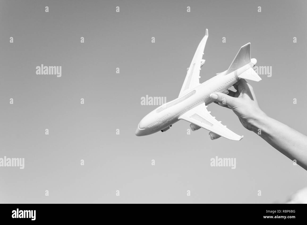 Plane model in hand. Airplane on blue sky. Jet or aircraft toy on sunny outdoor. Travel by air transport, aviation. Symbol of wanderlust, trip and vacation. Dream and imagination concept, copy space. - Stock Image