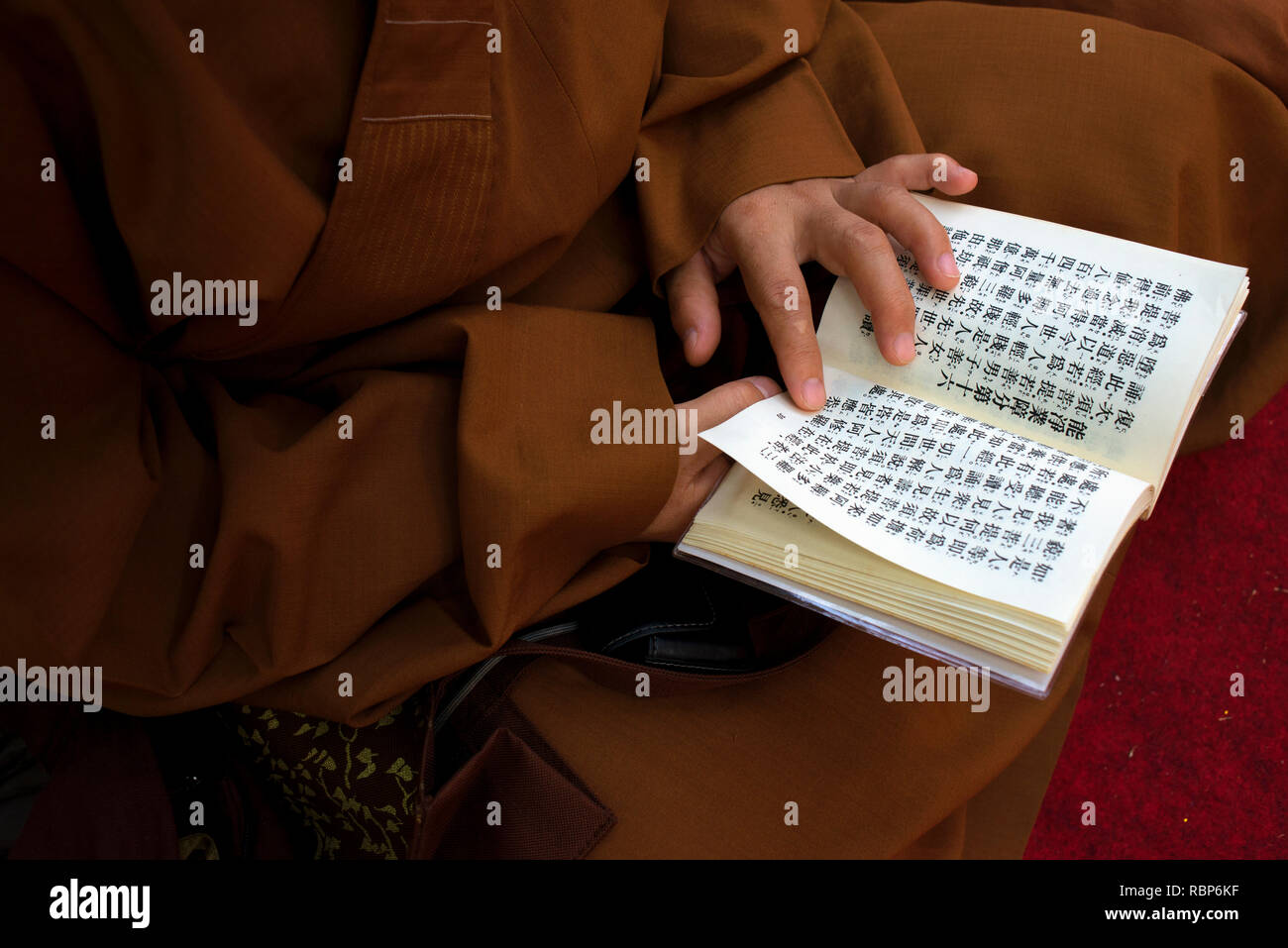 A Buddhist monk reads from religious text at Bodh Gya during Buddha Purnima celebrations. - Stock Image