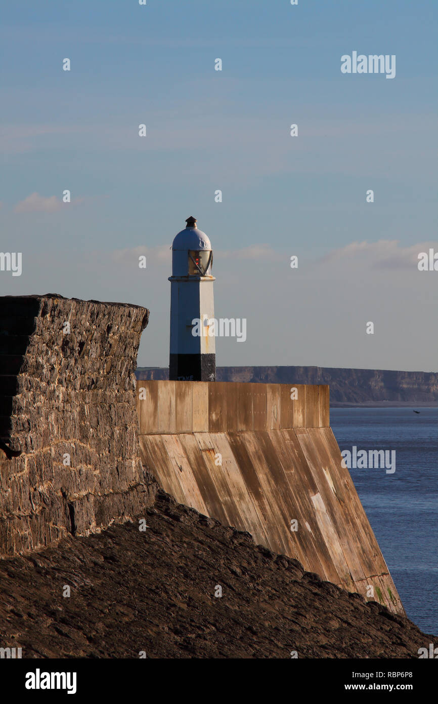 The very visible lighhouse stood out on the end of the sea wall at Porthcawl displaying two red lights as a warning to mariners on the Bristol channel - Stock Image