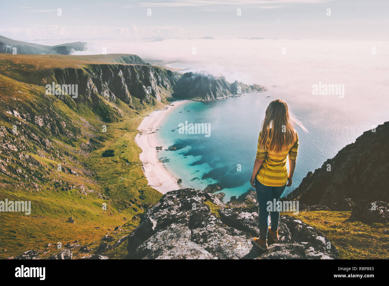 Summer travel woman tourist standing alone on mountain top over