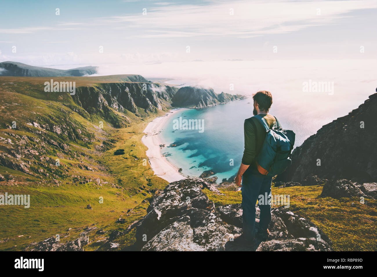 Summer travel man tourist standing alone on mountain top over