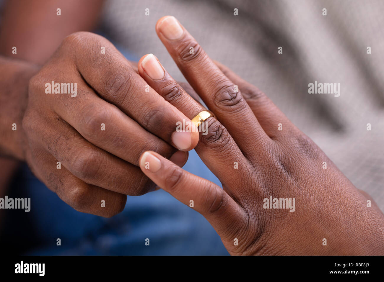 Close-up Of Man's Hand Putting Golden Engagement Ring On Woman's Finger - Stock Image