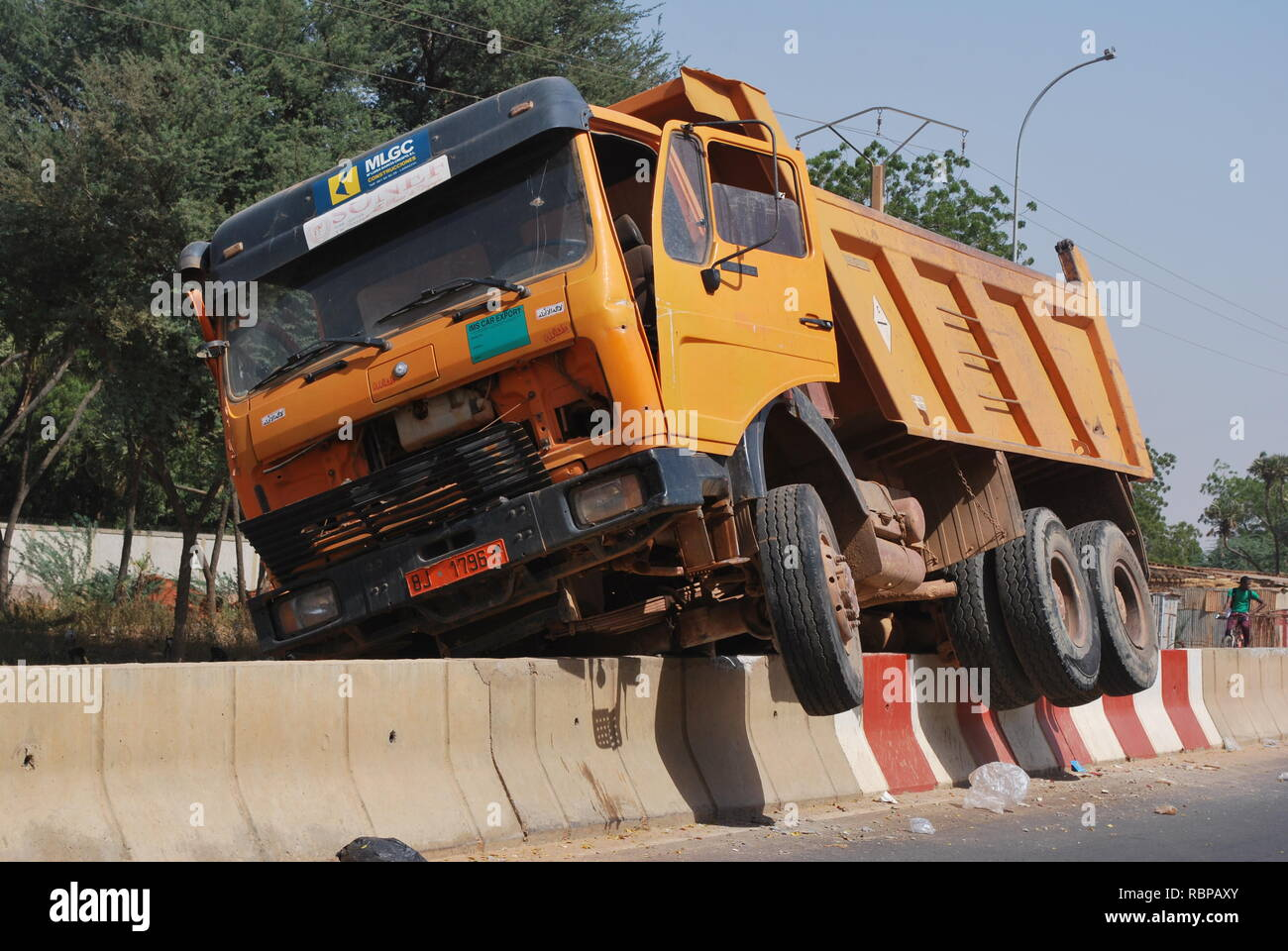 A dump truck high-centered on a cement barrier in Niamey, Niger,  Africa - Stock Image