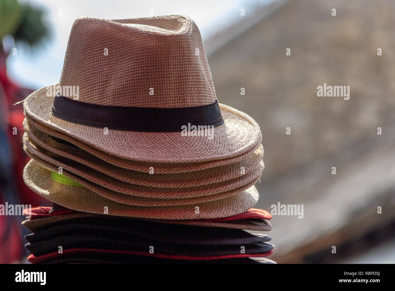 93f59e40 A stack of straw fedora hats in multiple colors with different colored  bands with a blurred