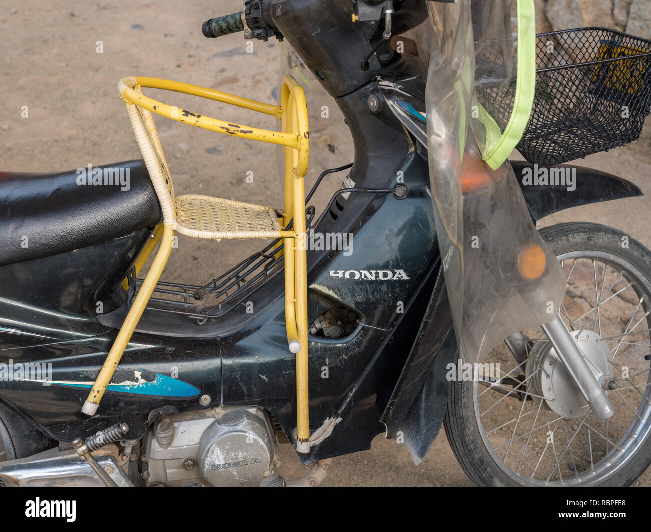 Metal childs chair wedged onto motor bike in China - Stock Image