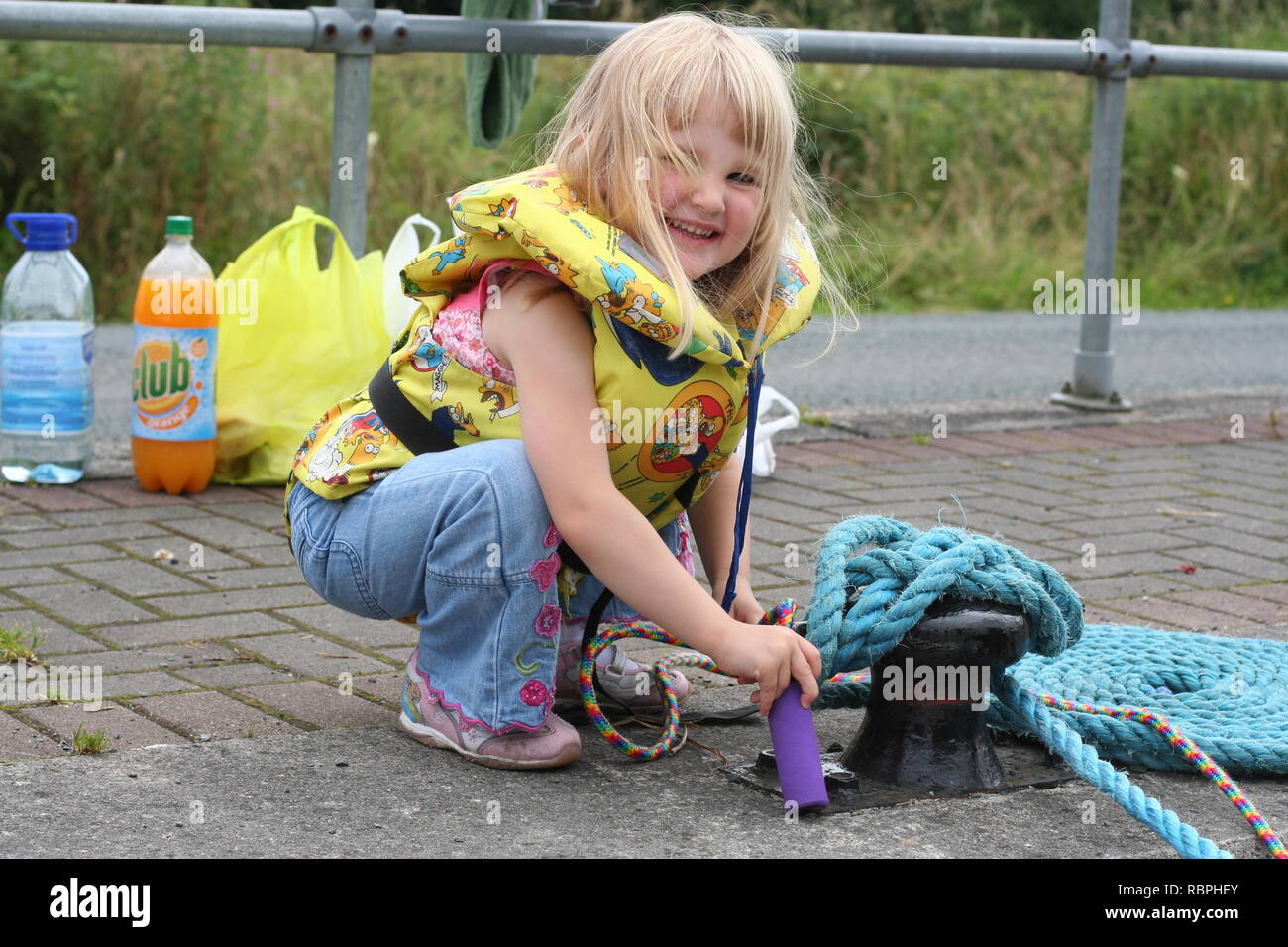 happy blonde little girl, kid wearing lifejacket life vesting, water safety concept rope, ropes, dock, boat moored, sail, sailing, picnic sailing - Stock Image