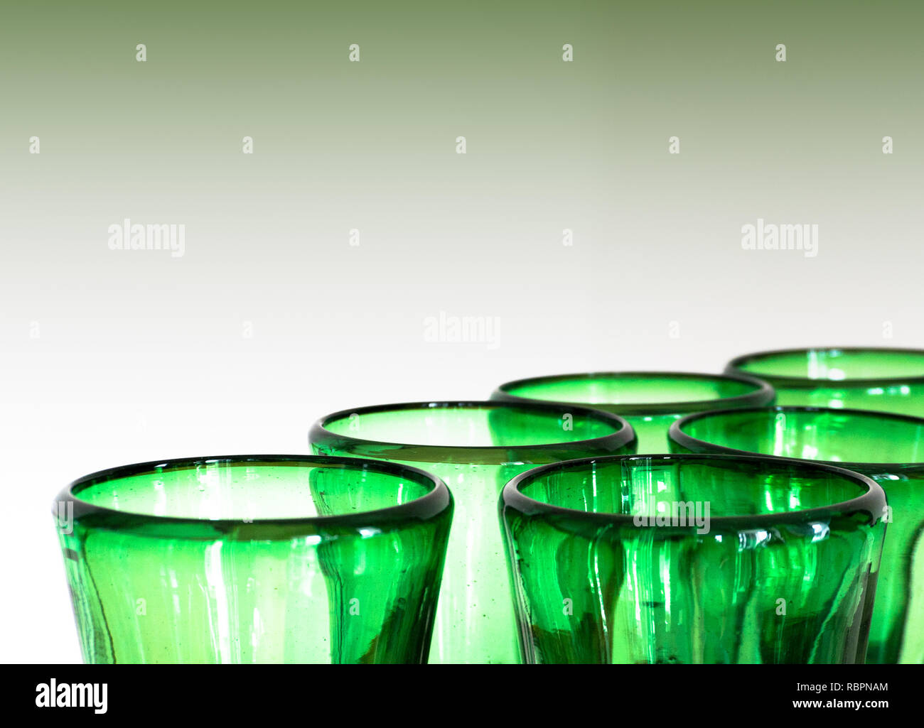 green glass designer wine glasses detail view abstract with copy space horizonal and green background - Stock Image