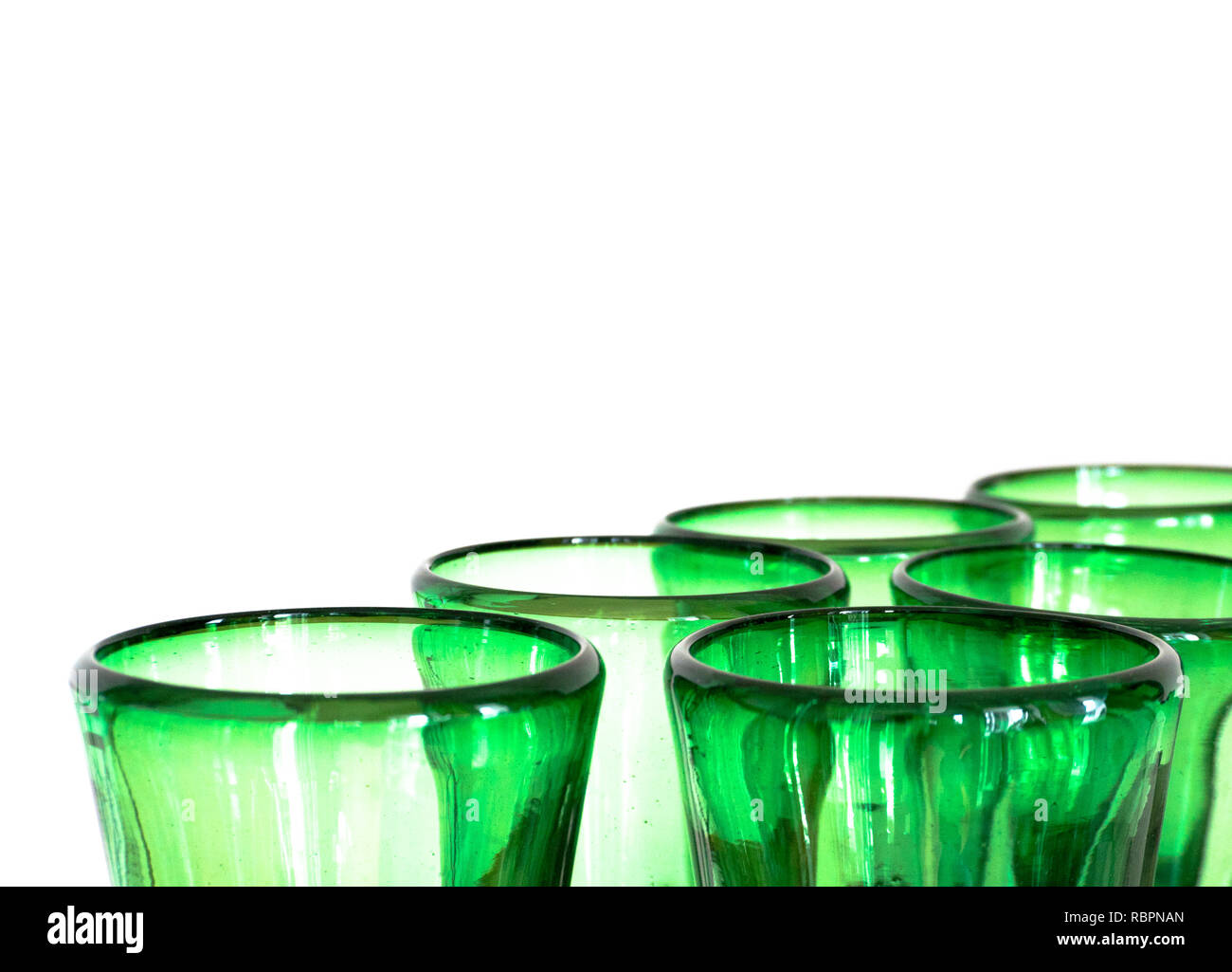green glass designer wine glasses detail view abstract with copy space horizonal and white background - Stock Image