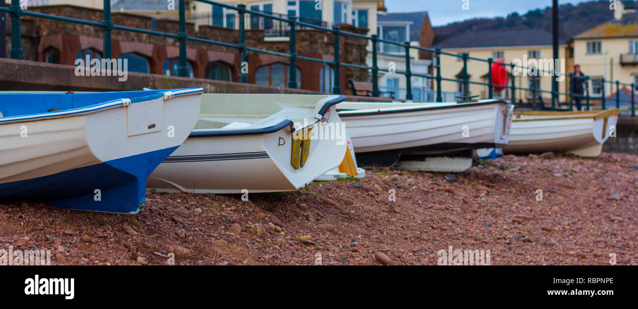 Small fishing boats lined  up on a pebble beach in Sidmouth, England - Stock Image