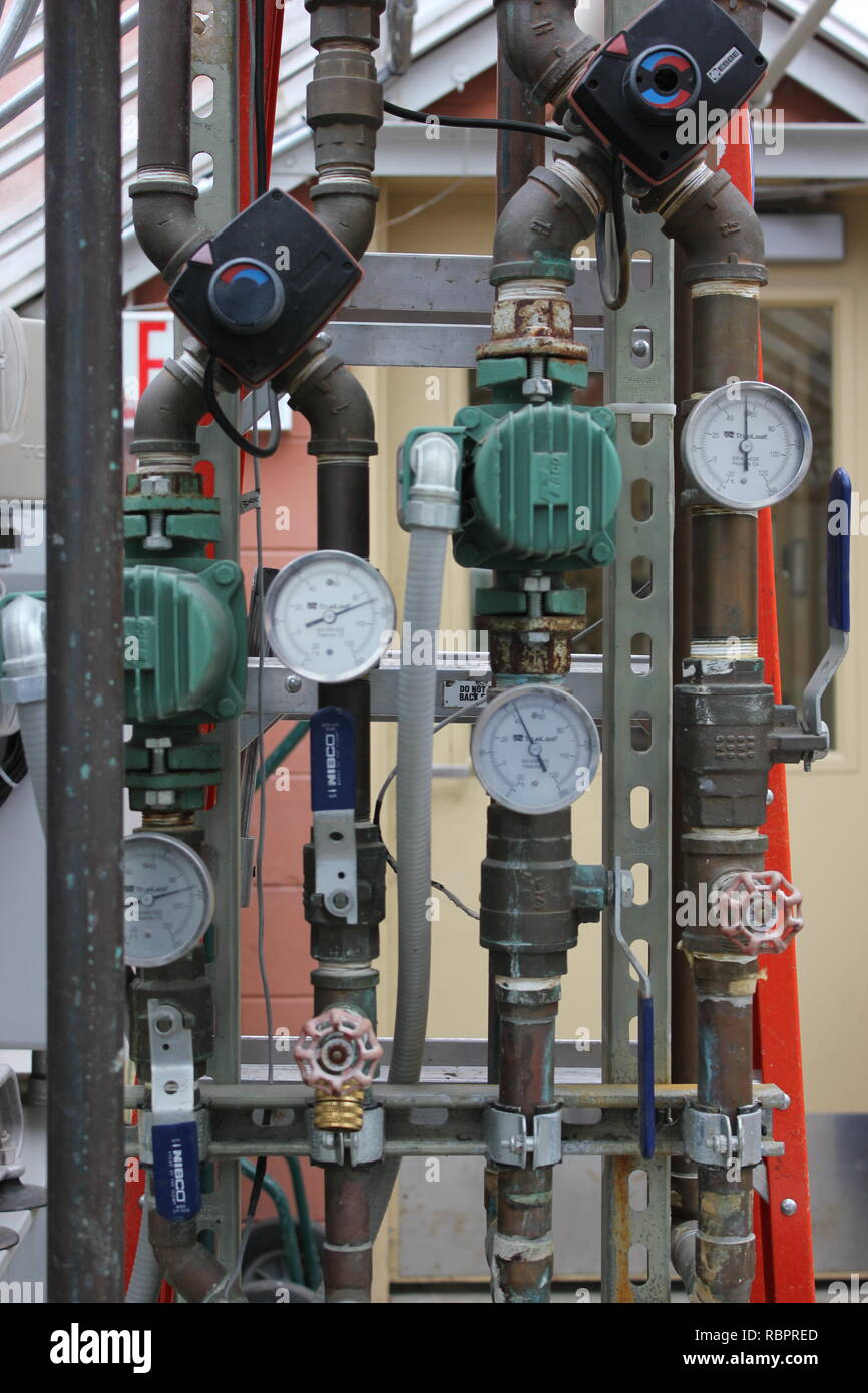 Behind the scenes display of pipes, valves, and gauges at the Oak Park Conservatory in Illinois, USA. - Stock Image