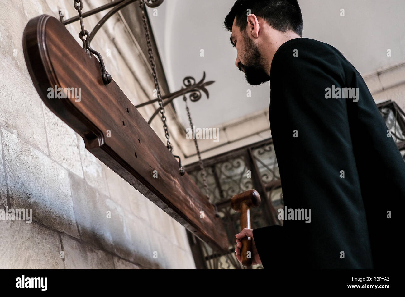 A priesthood seminarian strikes nakos or simandron, wooden boards used instead of bells when the Ottoman rulers forbade the ringing of church bells, t - Stock Image