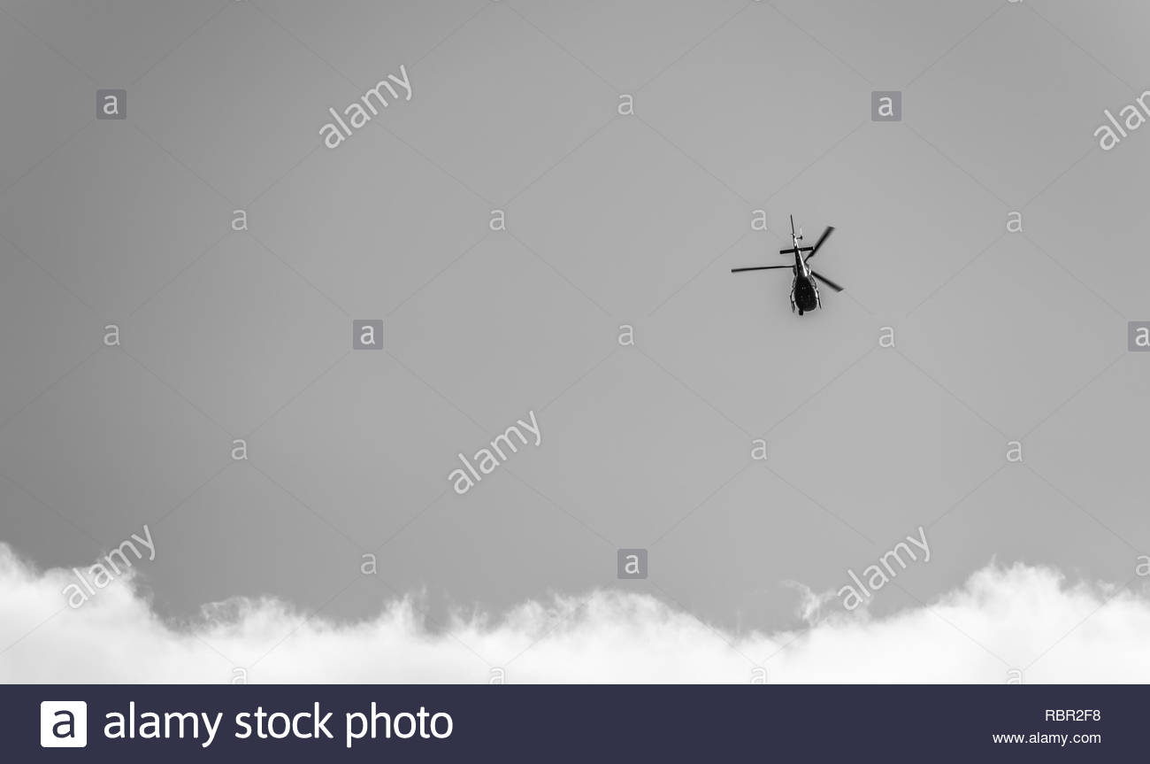 Helicopter approacing clouds - Stock Image