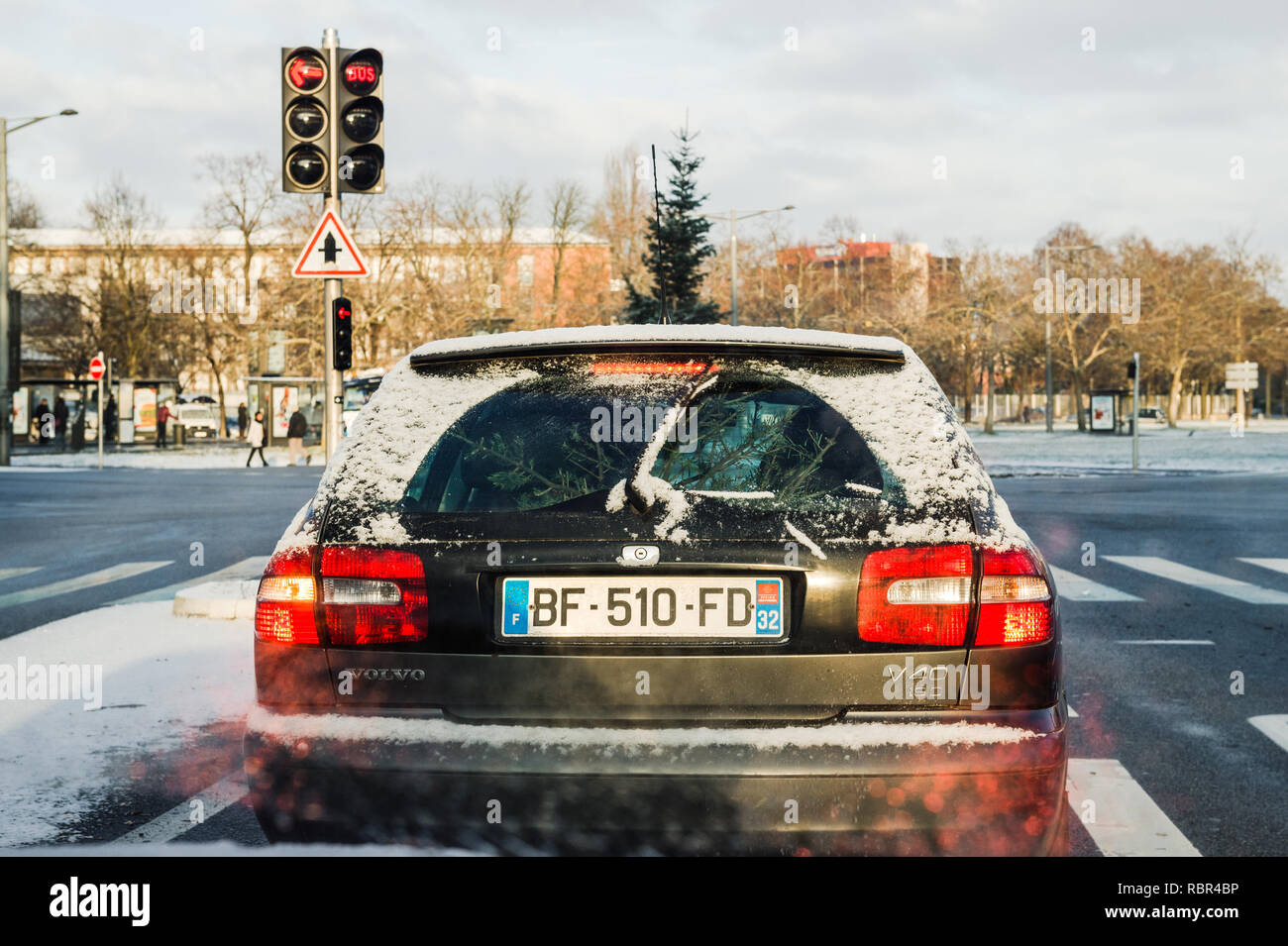 PARIS, FRANCE - JAN 16, 2017: Rear view of a Volvo V40 wagon car waiting at red light transporting in the trunk a fir tree for Christmas - getting ready for Christmas, buying fir tree - Stock Image