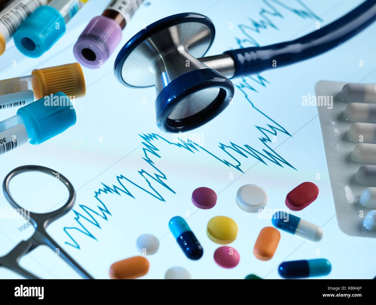 Stethoscope, medicine and medical samples sitting on a share price graph, illustrating investing in pharmaceutical research. - Stock Image