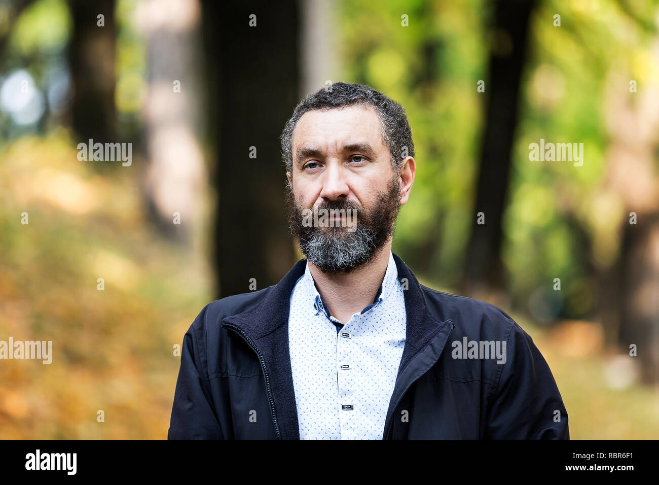 Portrait of handsome 40 year old man with curly hair and grizzled. - Stock Image