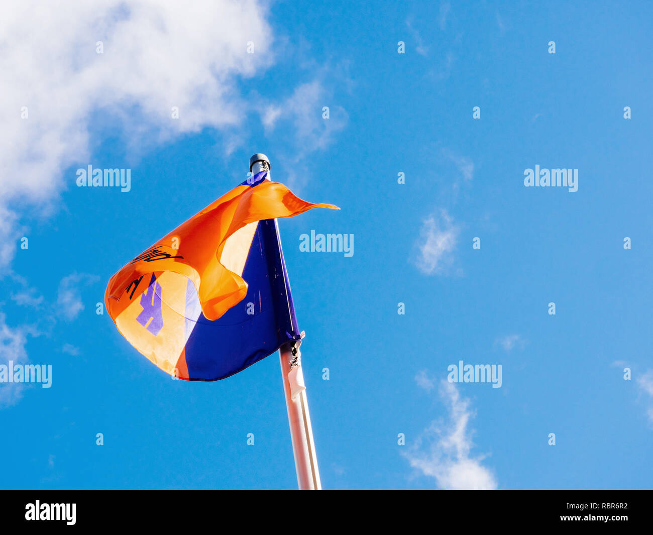 HAMBURG, GERMANY - MAR 20, 2018: Hapag-Low angle view of Lloyd transnational German-based transportation company flag waving against blue sky - Stock Image