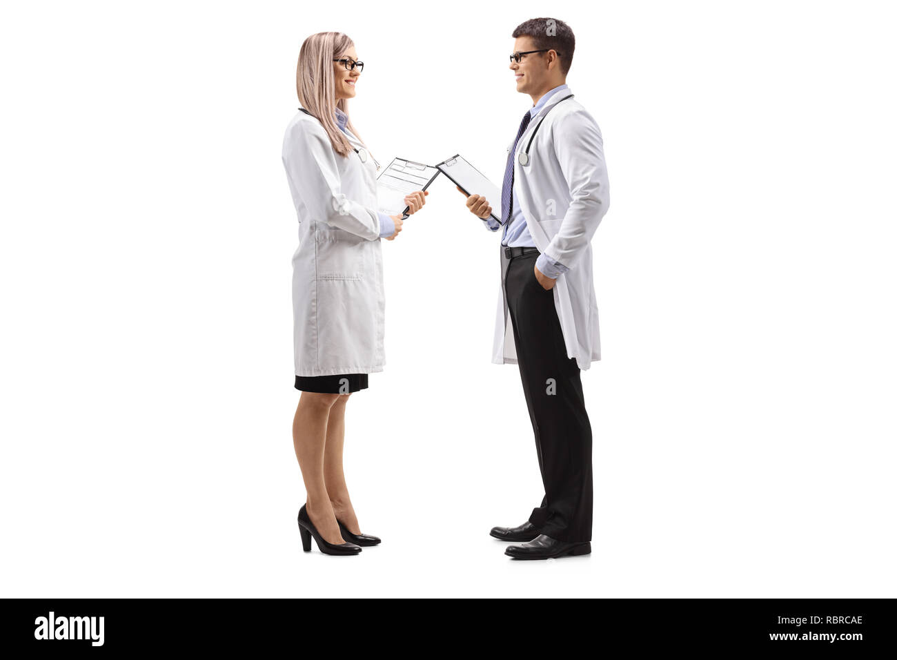 Full length profile shot of a female and male doctor in a lab coat talking isolated on white background - Stock Image