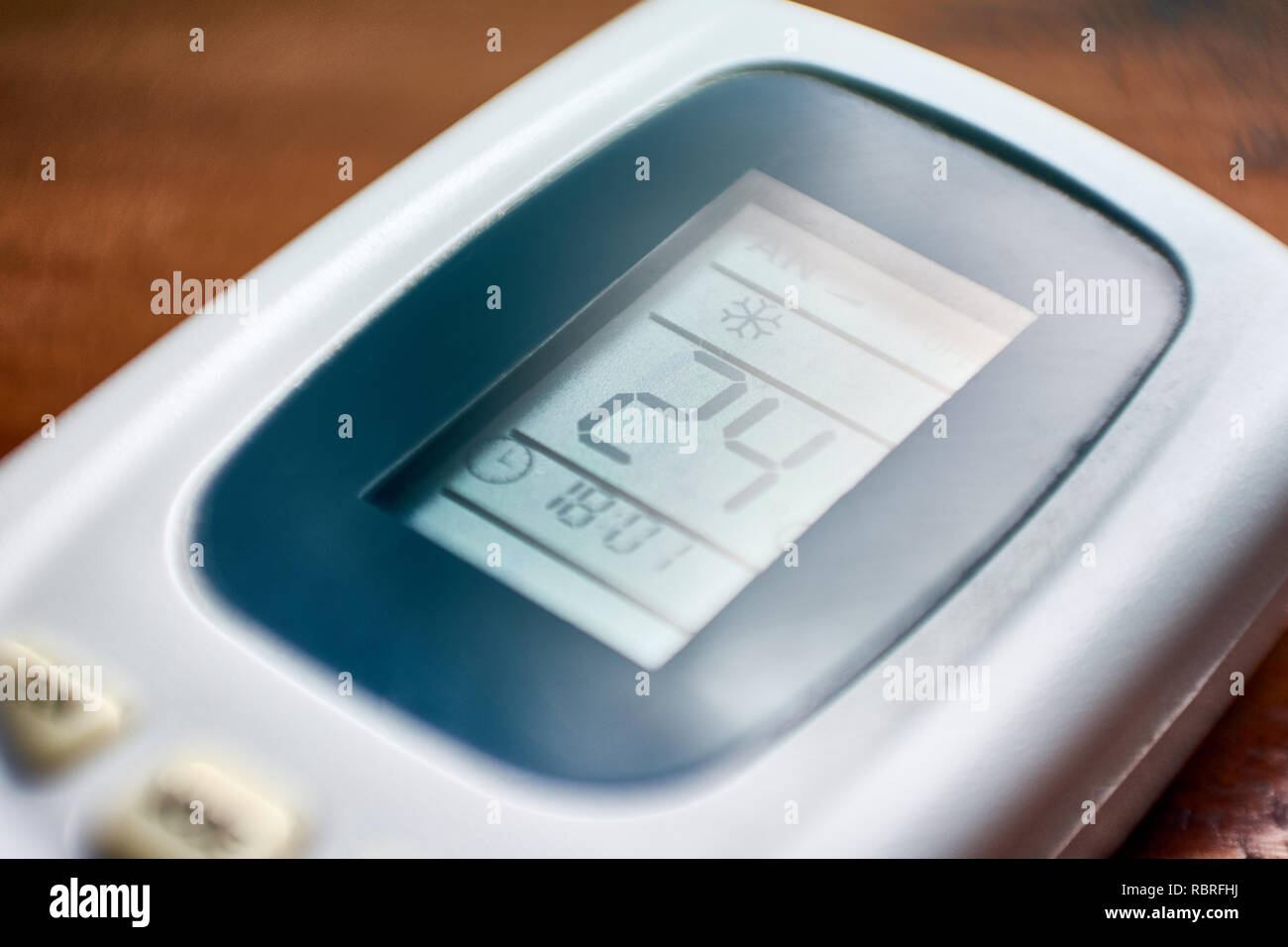 The remote control of an air conditioner set to 24 degrees celsius, a recommended setting to protect the environment. Stock Photo