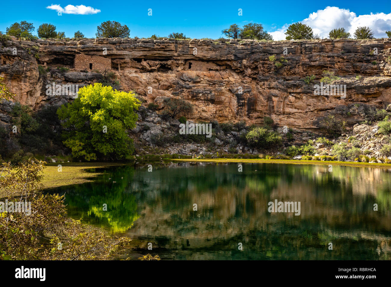 Ancient ruins and surroundings reflect on the quiet water of Montezuma Well. Part of Montezuma Castle National Monument. Stock Photo