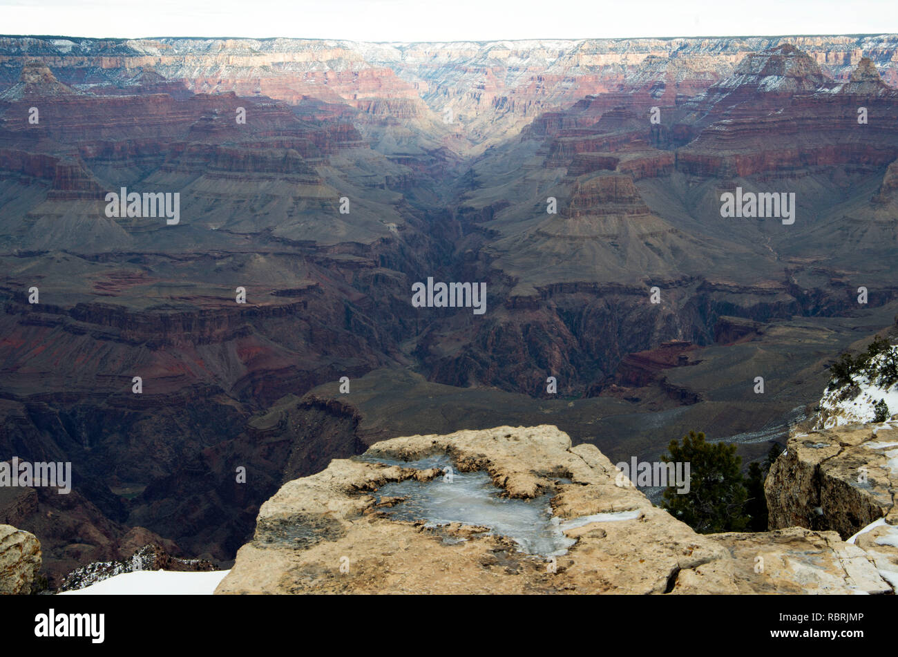 The South Rim Trail of the Grand Canyon offers excellent views of the canyon, but winter ice can make areas slippery. - Stock Image