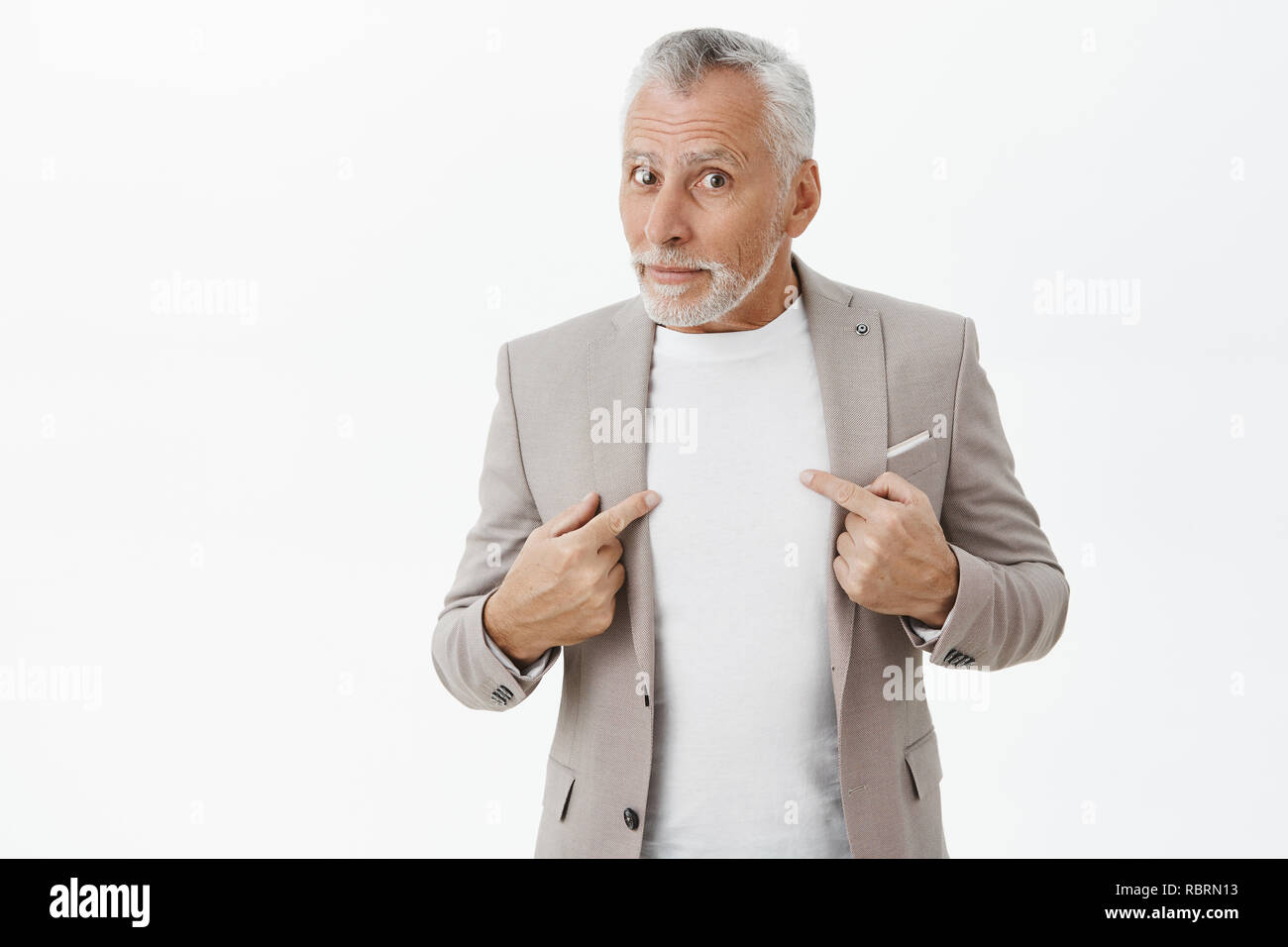Man surprised and questioned being picked by boss standing unsure over grey wall in elegant formal suit pointing at himself and gazing confused at camera asking uncertain if people talking about him - Stock Image
