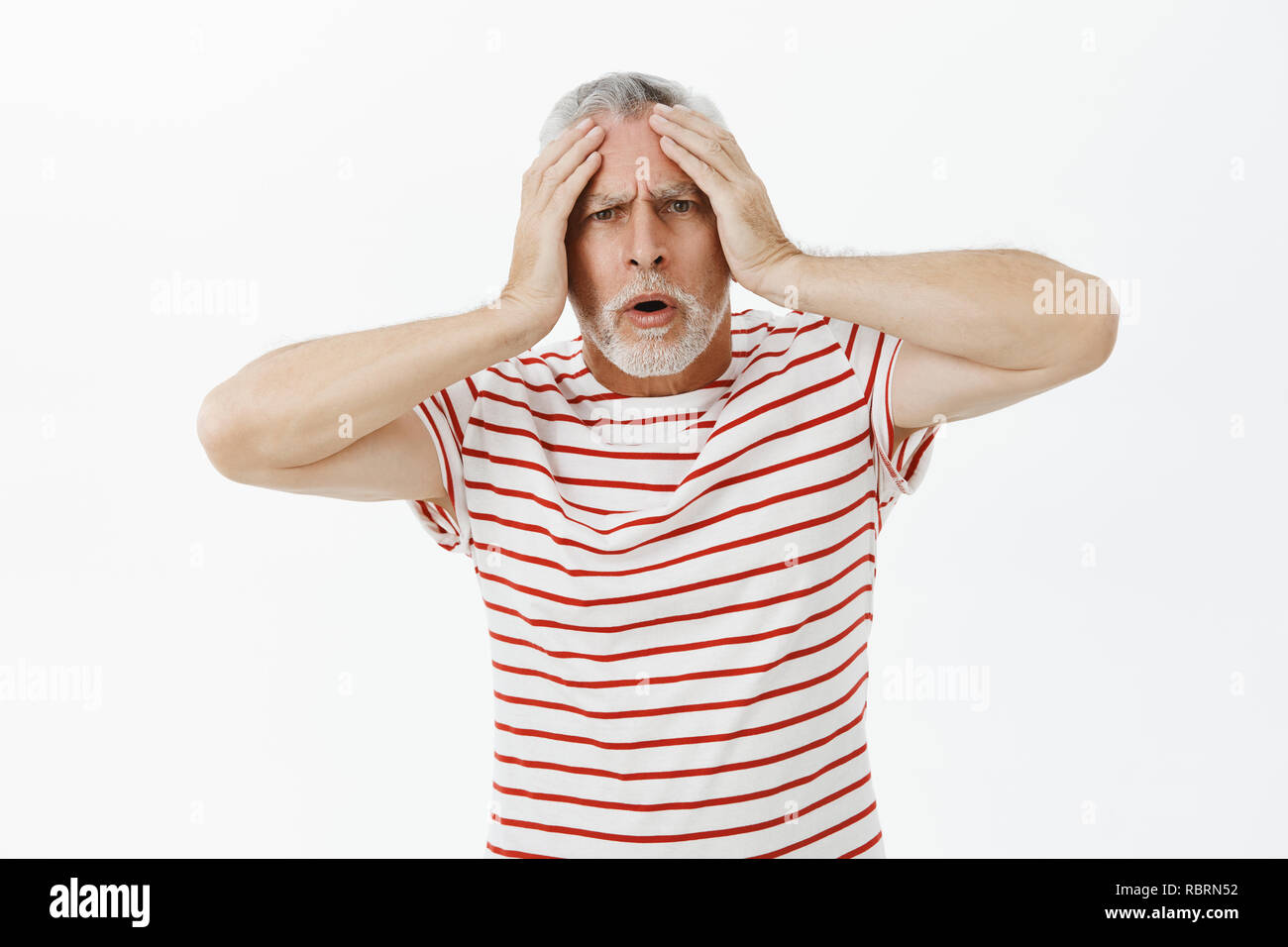 Intense bothered and shocked displeased old man touching head and frowning open mouth looking cocnerned and troubled at camera being in panic not knowing what do how solve problem - Stock Image