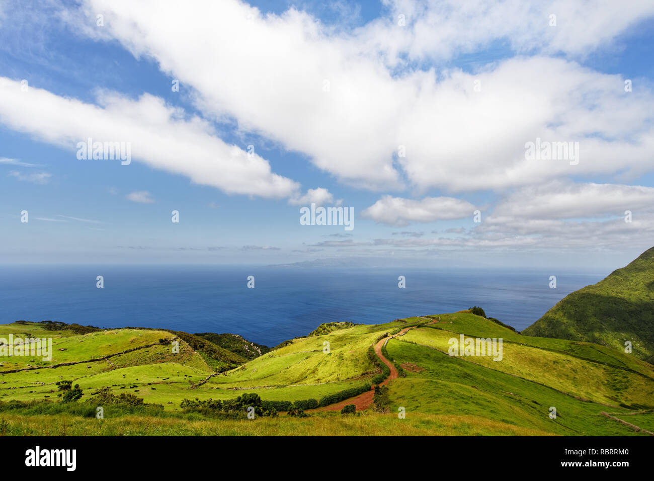 Azores - View from the north side of the island of Sao Jorge to the imposing volcano Pico on the neighboring island of the same name, a red dirt road  - Stock Image