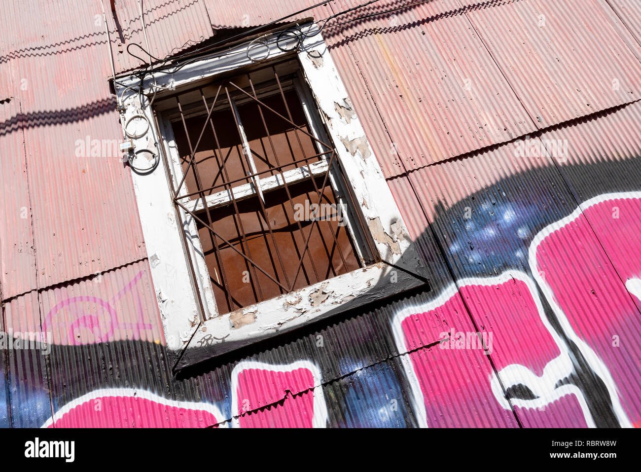 A window of a building clad in metal sheeting in Valparaiso, Chile. - Stock Image