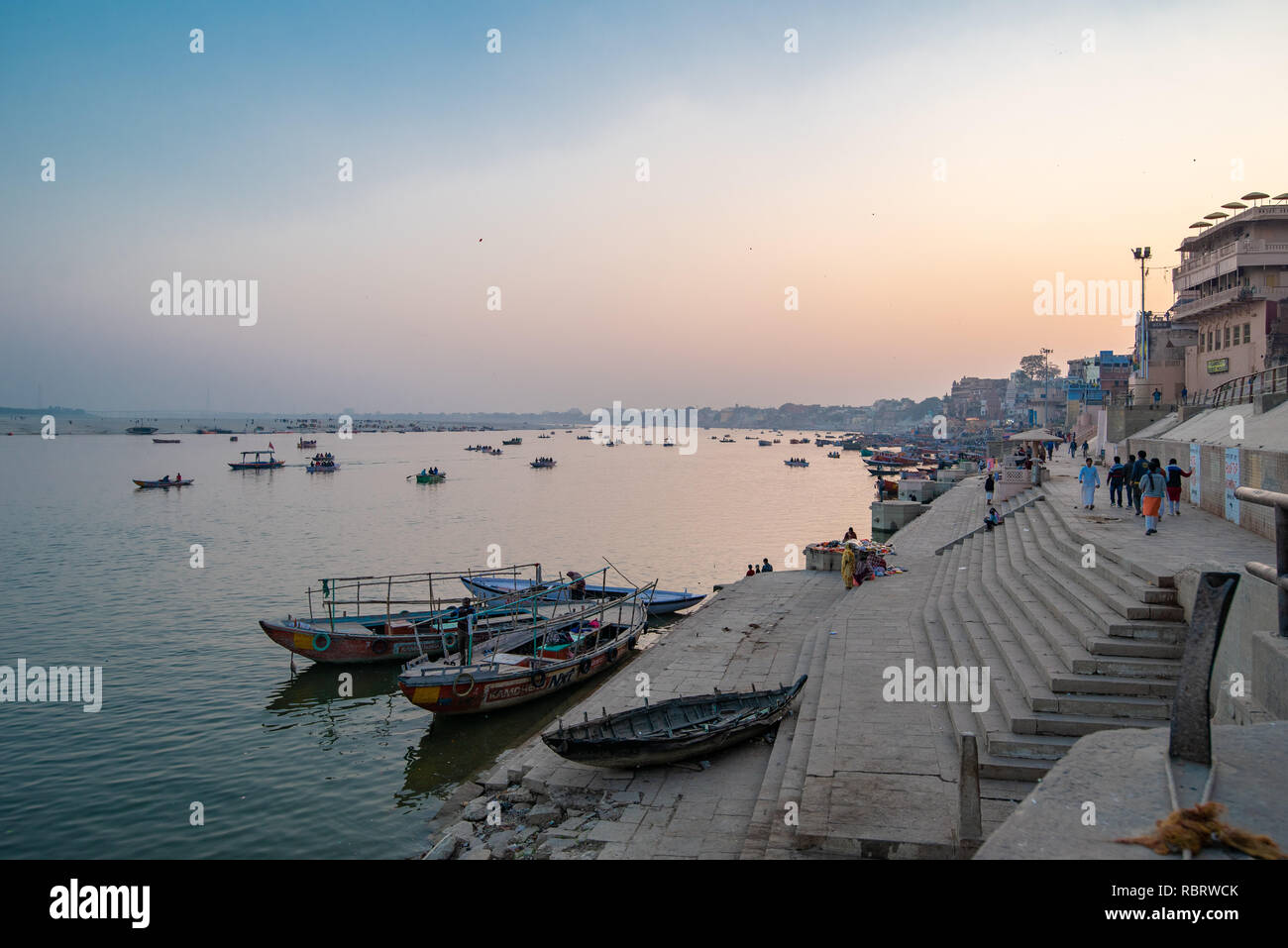 Boats at blue hour after sunset along the Ganges Ghat in Varanasi, India - Stock Image