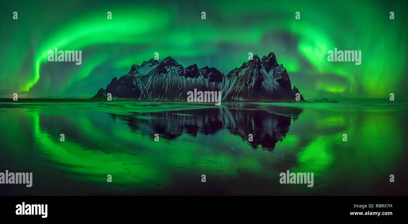Reflections of aurora borealis around Vestrahorn mountains on Stokksnes black beach, Iceland Stock Photo