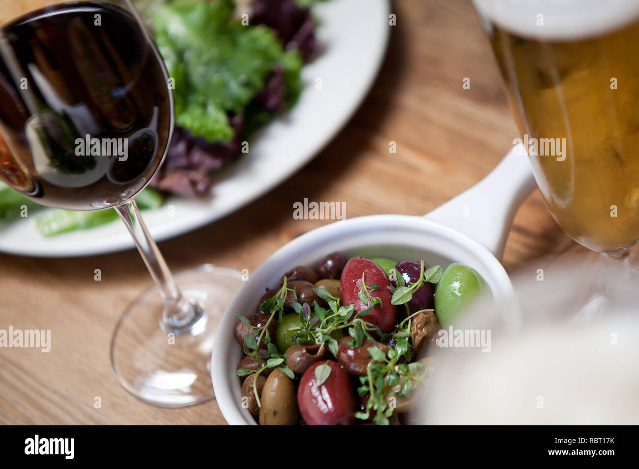 Close up of Italian Olives with Tyme served with meal and wine - Stock Image