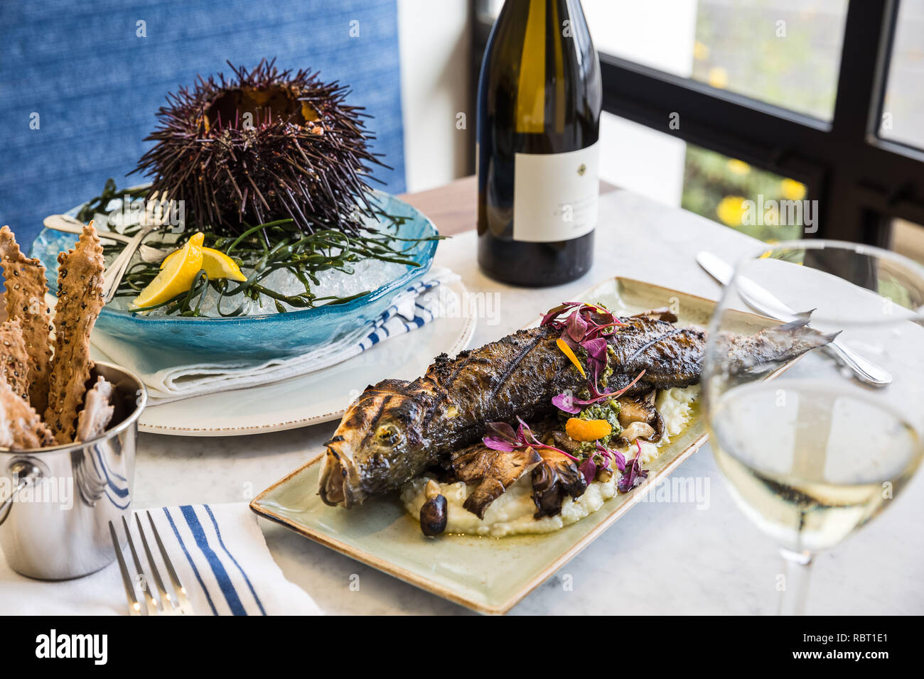 Seafood Table Setting with Grilled Snapper and Uni Sea Urchin - Stock Image