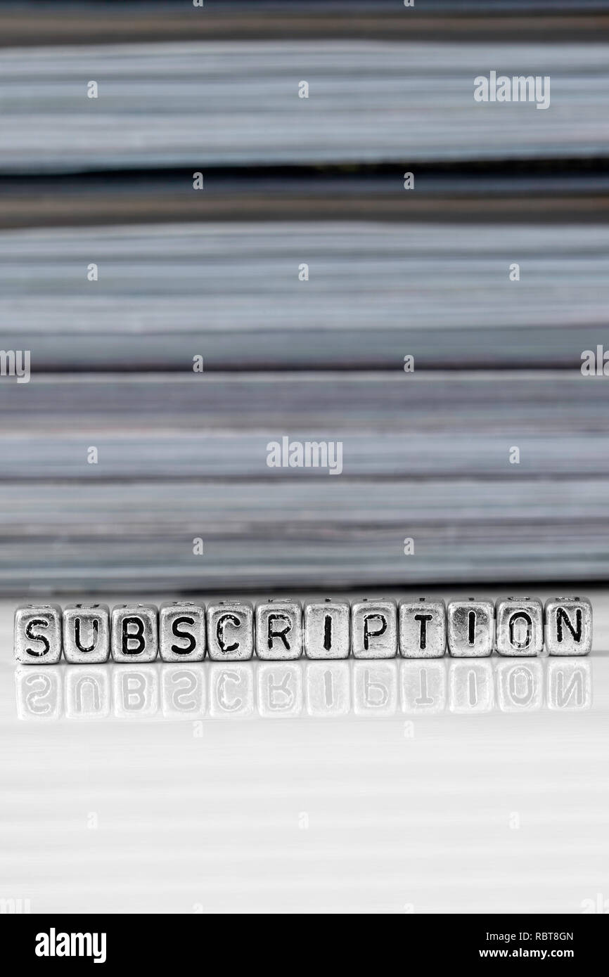 Subscription on beads with magazines stacked in the background reflected on a white surface - Stock Image