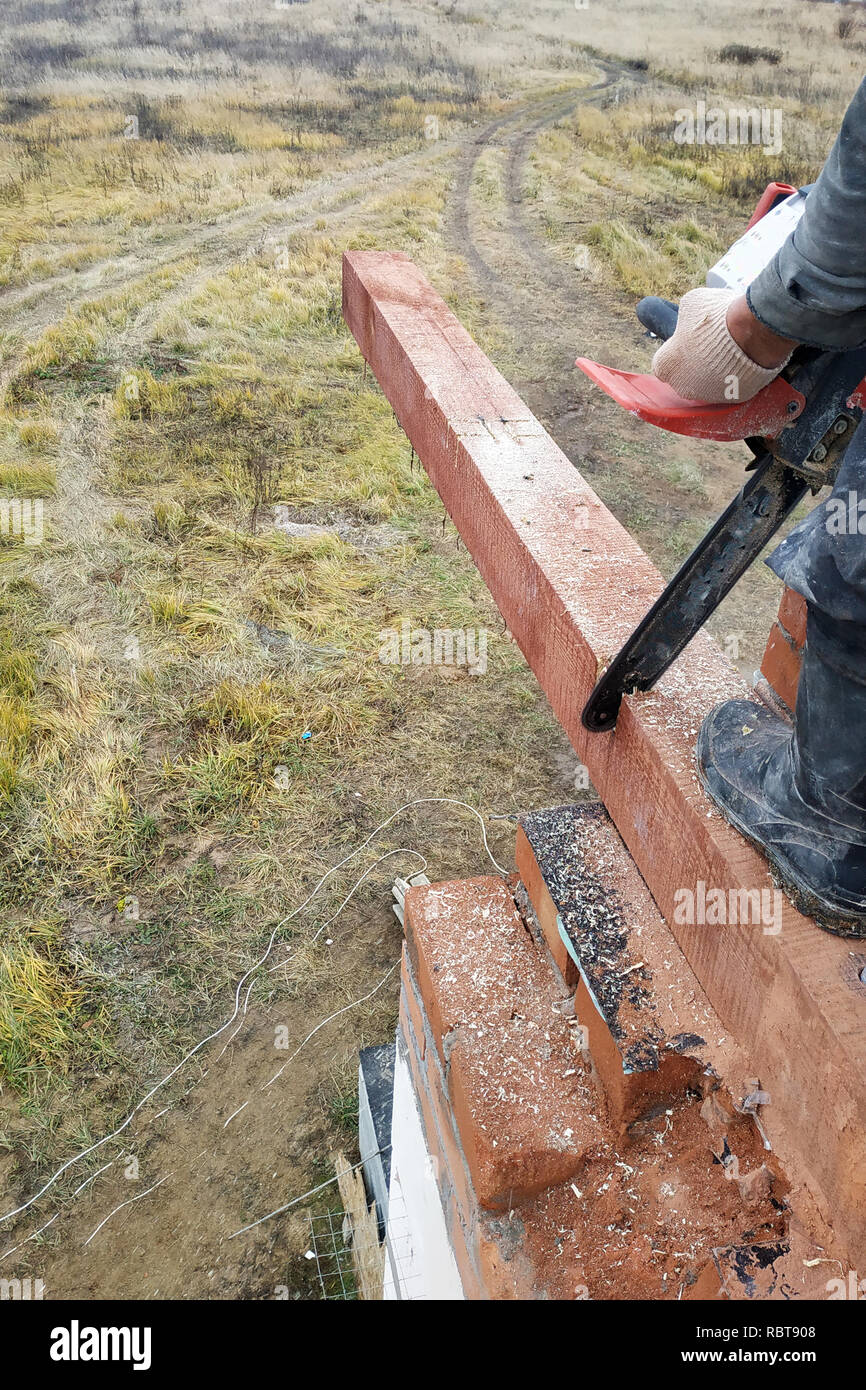woodworker with a chainsaw makes drank on a wooden beam construction of houses 2018 - Stock Image
