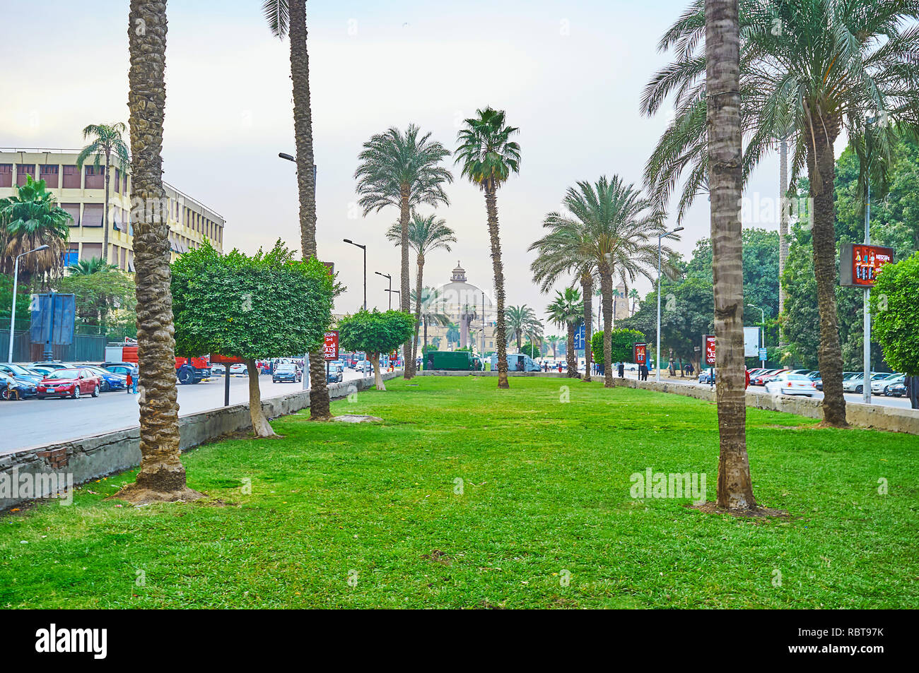 GIZA, EGYPT - DECEMBER 19, 2017: Walk along the scenic garden in Nahdet Masr square with a view on the dome of Faculty of Arts building of Cairo Unive Stock Photo