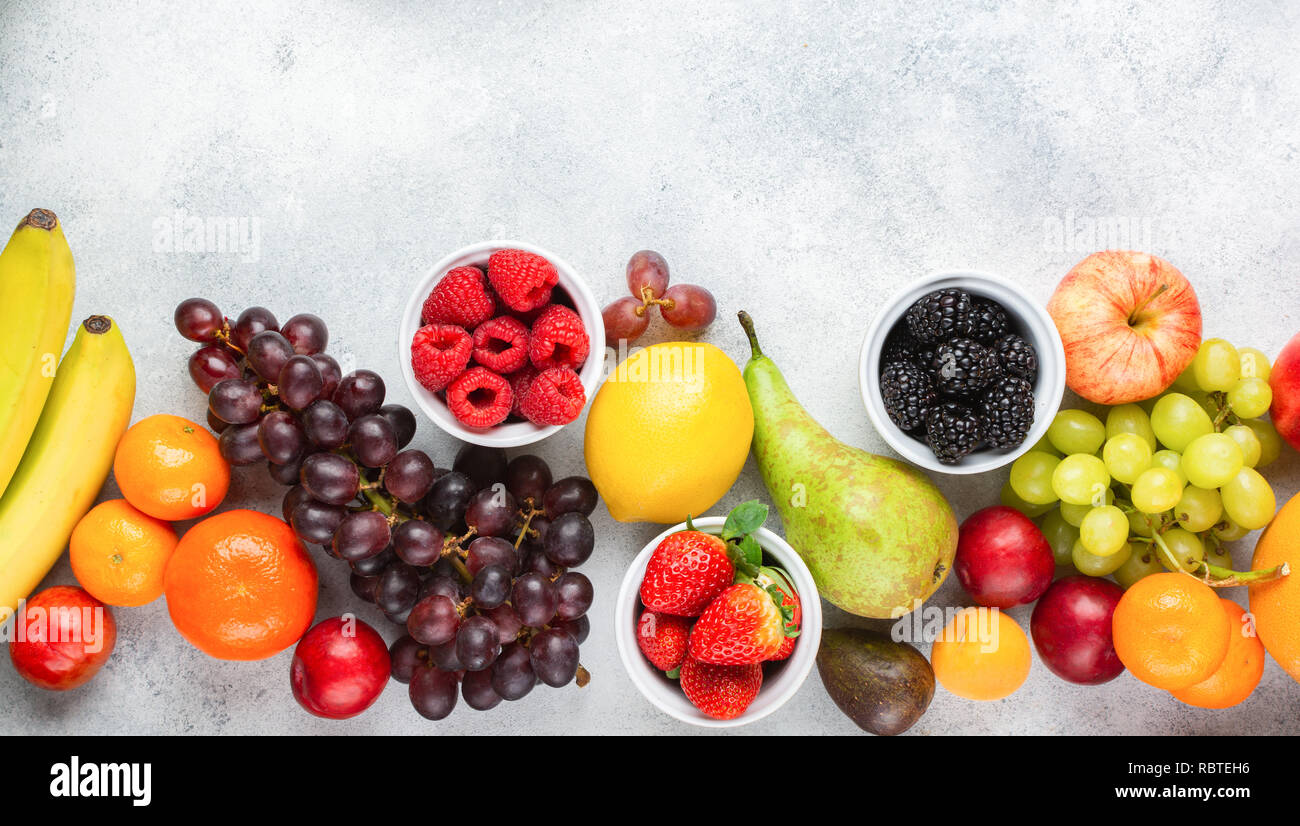 Top view of delicious fruits, raspberries oranges plums apples pears grapes blueberries bananas strawberries on white table, top view, copy space - Stock Image